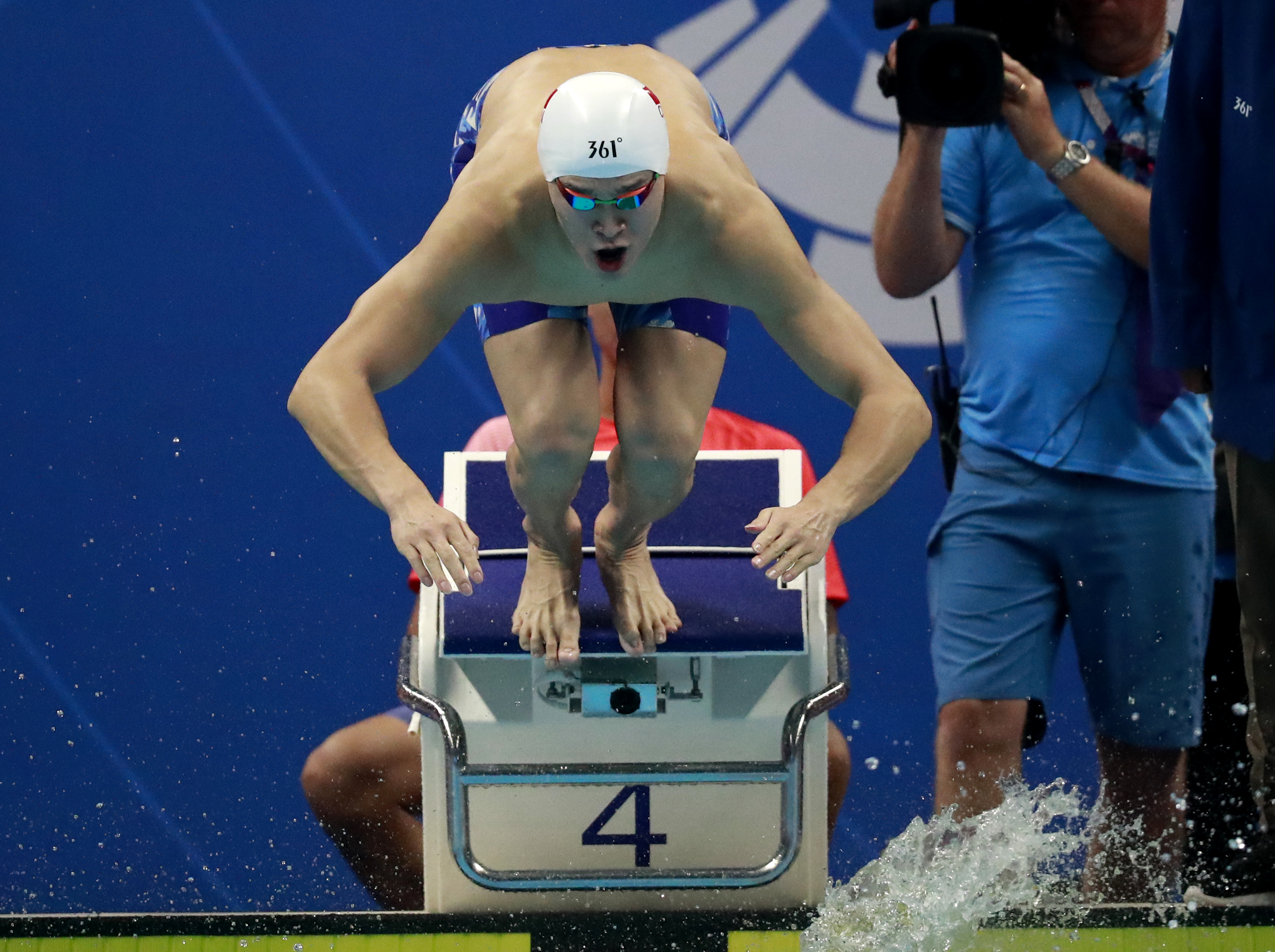 China`s Sun Yang stands dives in to swim