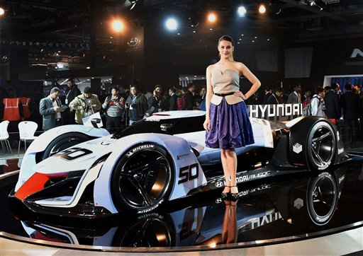 A model poses in front of a sports car displayed at the Hyundai stall atAuto Expo 2016 in Greater Noida. PTI