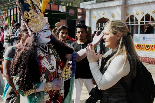 A foreign visitor interacts with a performer dressed up like Lord Krishna at the inauguration of 30th International Surajkund Crafts Mela in Faridabad. PTI