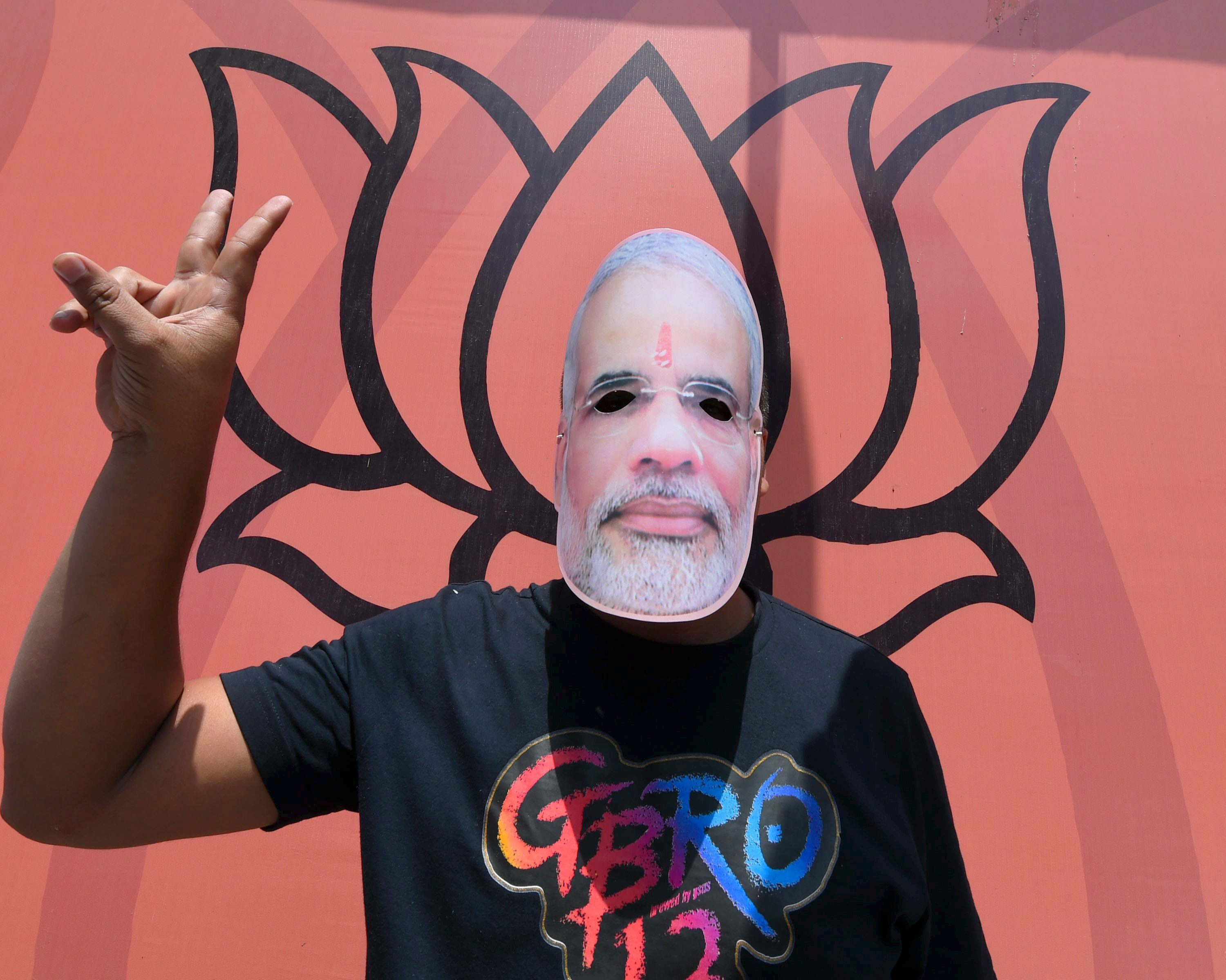 A BJP supporter, wearing mask of PM Narendra Modi, flashes victory sign as he celebrates the party's performance in Assembly polls of the five states, at party headquarters in New Delhi on Thursday. PTI