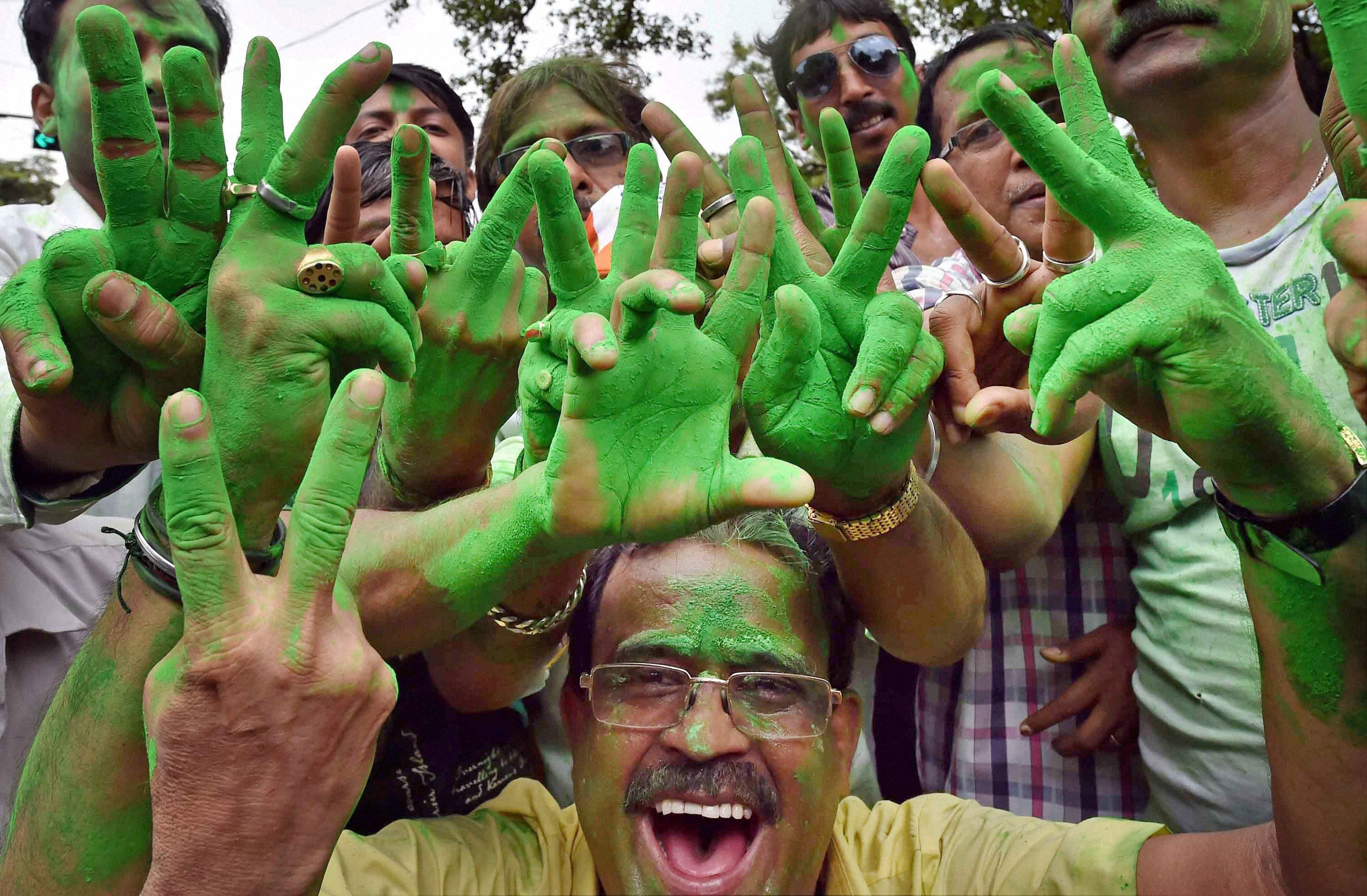 : Trinamool Congress supporters make 'V' sign as they celebrate the party's thumping victory in West Bengal Assembly eections in Kolkata on Thursday. PTI