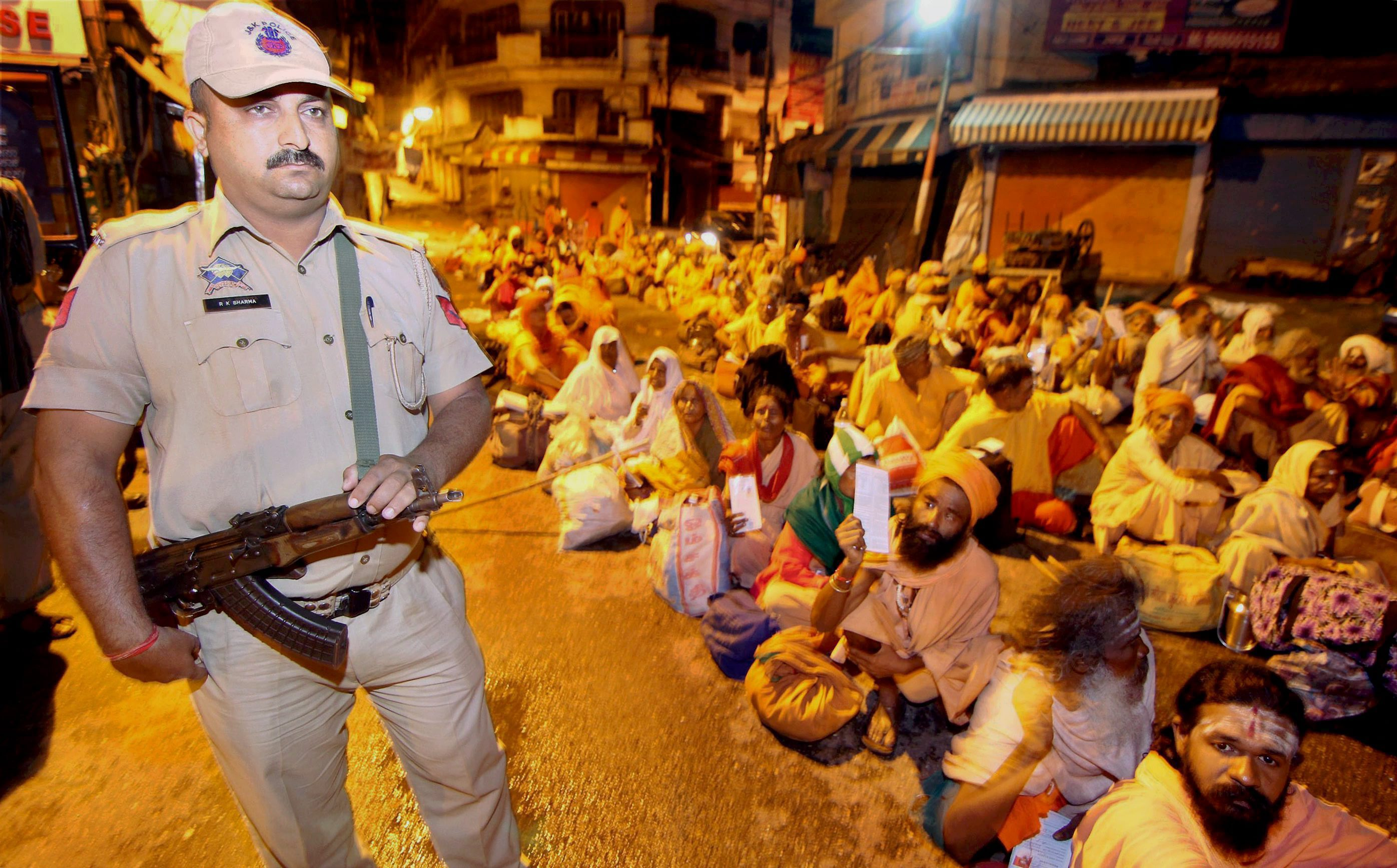 A security personnel stands guard as Sadhus (holy men) wait to board a bus for annual Amarnath pilgrim yatra in Jammu- PTI