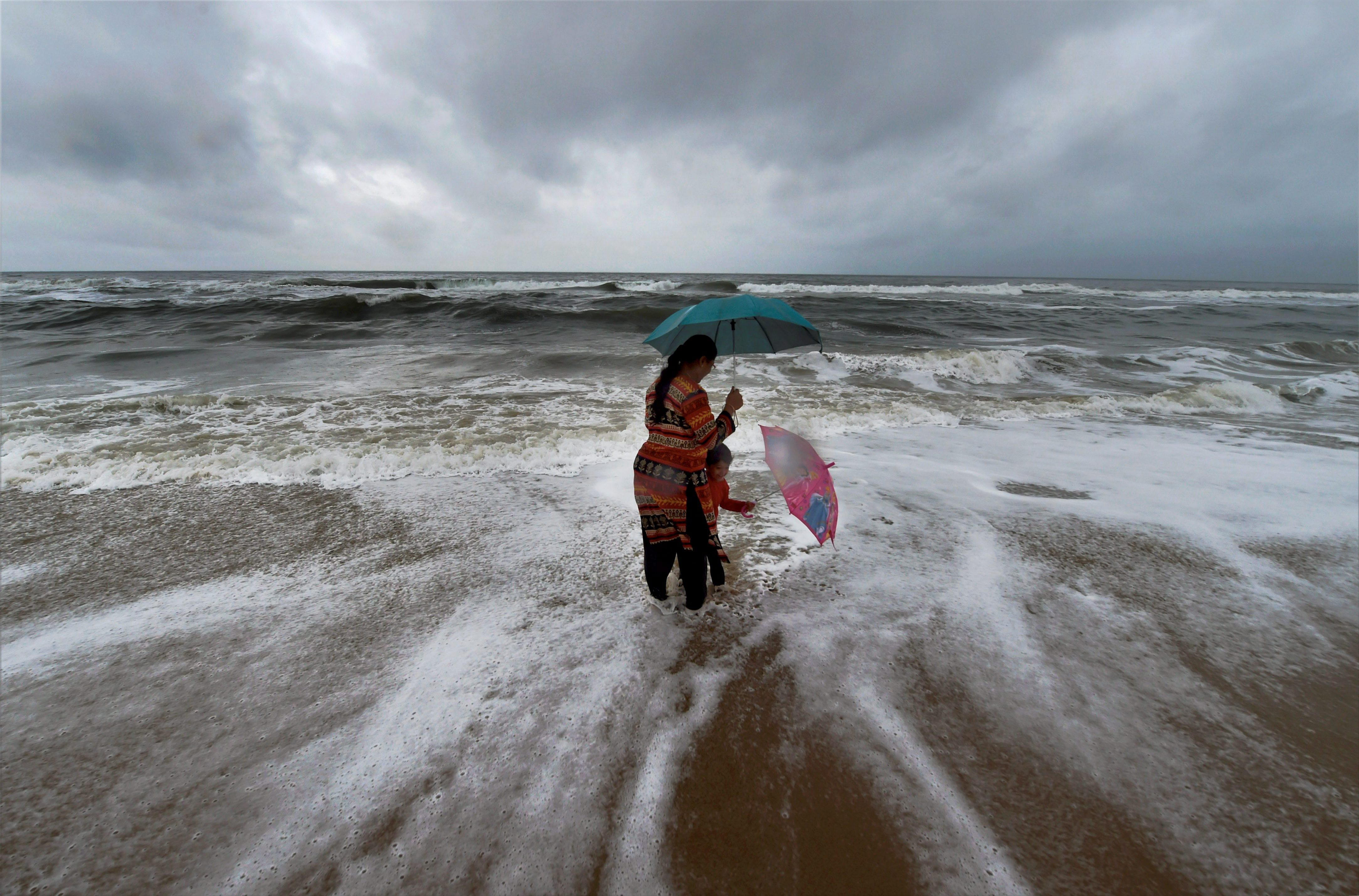 A woman standing with her son at Marina beach following heavy downpour due to the onset of Northeast monsoon in Chennai - PTI