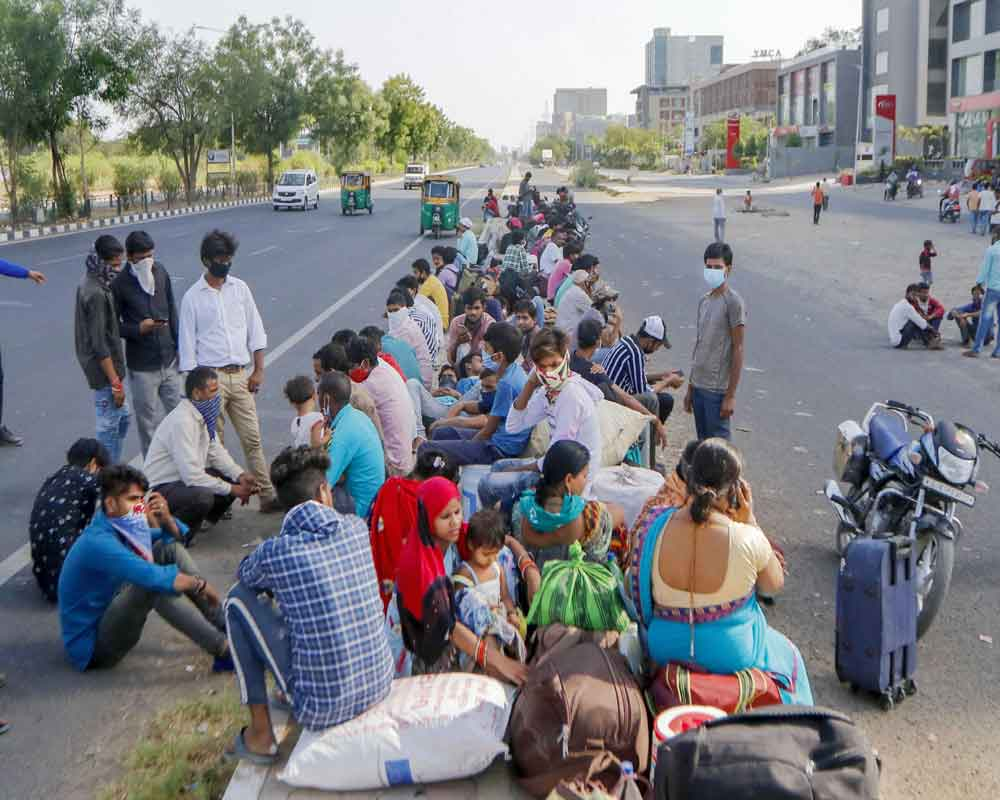 Migrants wait for a transport to reach the railway station and board a special train to their native places in Uttar Pradesh, amid the ongoing COVID-19 lockdown, in Ahmedabad - PTI