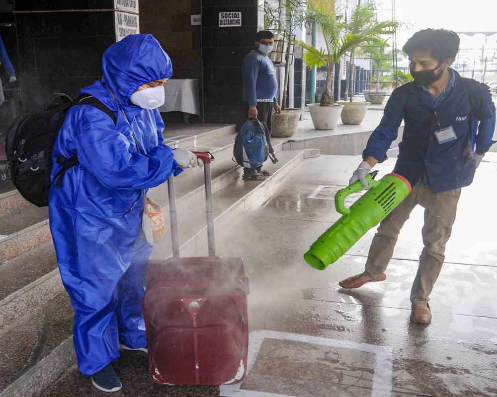 A worker sprays disinfectant on the bag of a passenger at Rajendra Nagar Terminal following the resumption of passenger train services by Indian Railways connecting major cities, during the ongoing COVID-19 nationwide lockdown, in Patna - PTI