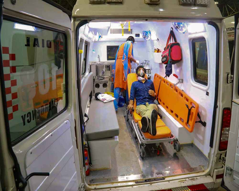 A passenger is seen under medical care inside an ambulance after arriving from Kuwait by an Air India flight at Calicut International Airport, during the ongoing COVID-19 lockdown, in Kozhikode - PTI
