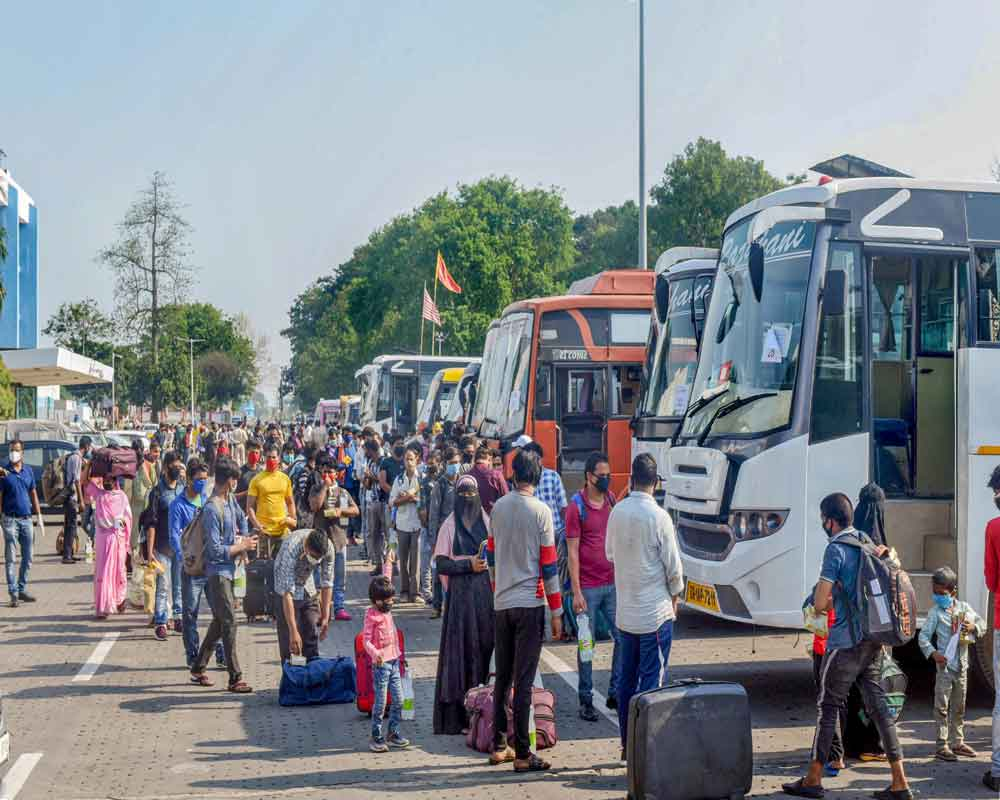 Migrants stand in queues to board buses to reach their native places after arriving from Bengaluru via special train at Hatia Railway station, during the ongoing COVID-19 nationwide lockdown, in Ranchi - PTI