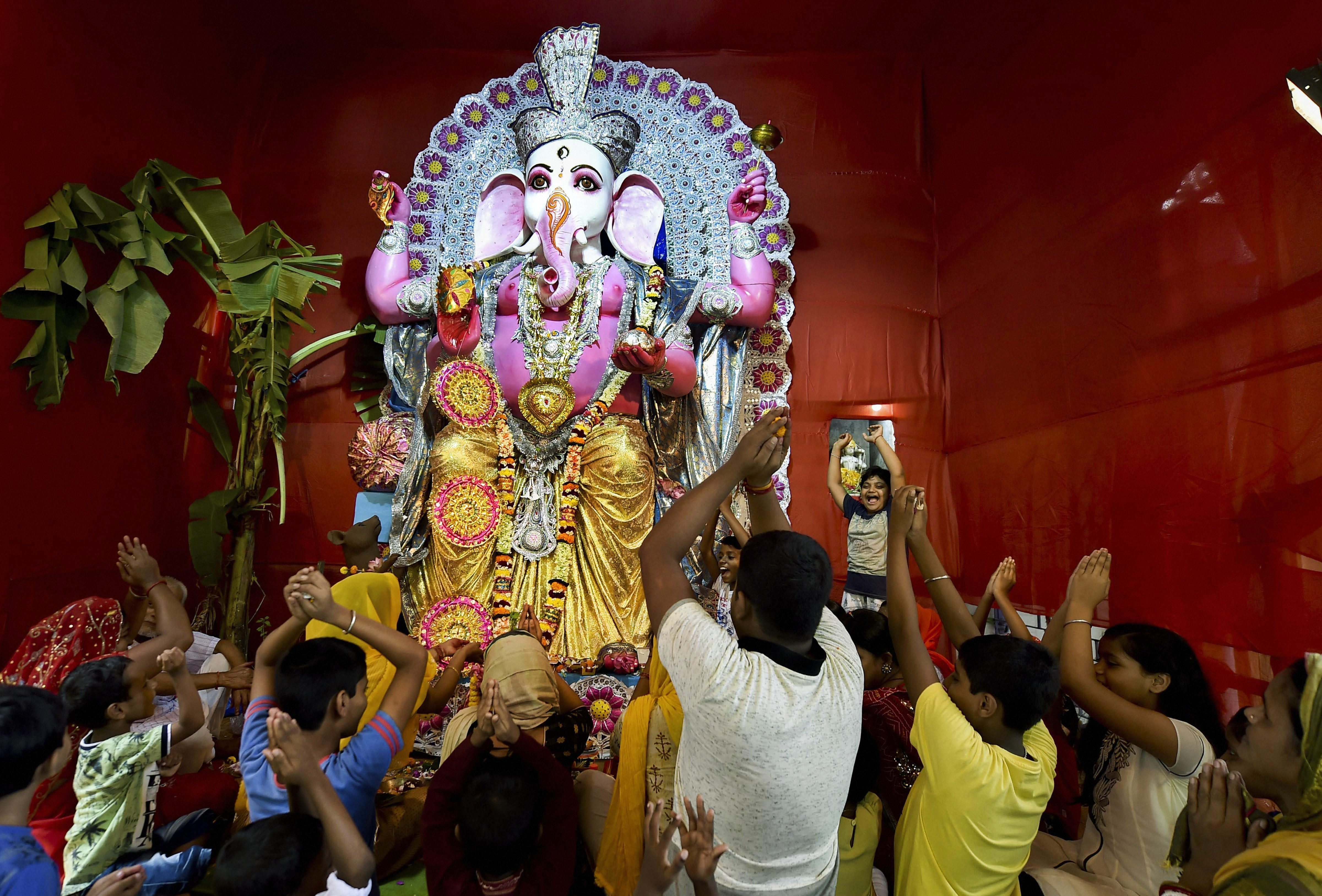 Devotees offer prayers to Lord Ganesh at a community puja pandal on the occasion of Ganesh Chaturthi in Kolkata - PTI