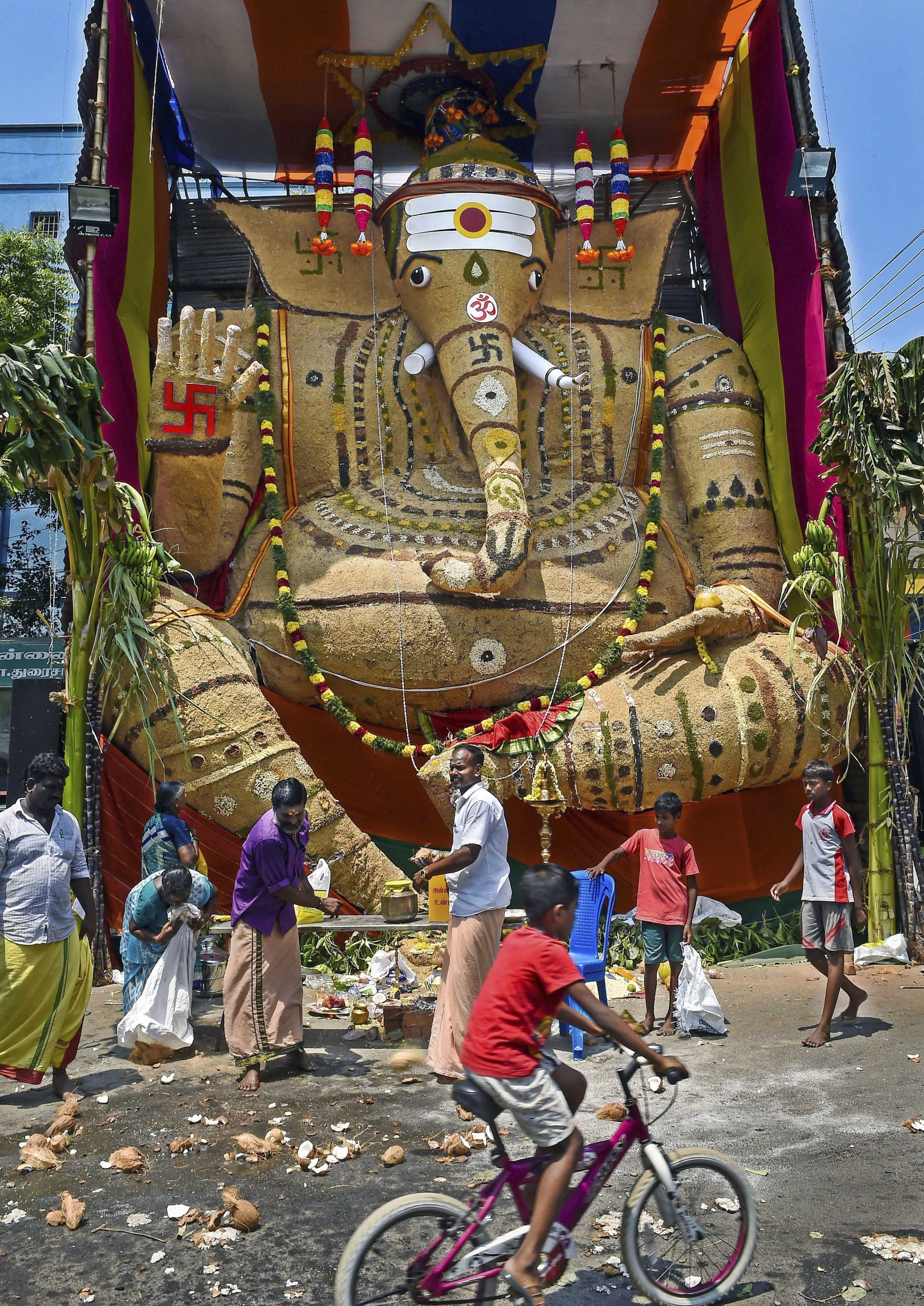Devotees near an idol of Lord Ganesha, made from whole grains, on the occasion of 'Vinayaka Chaturthi' celebrations, in Chennai - PTI