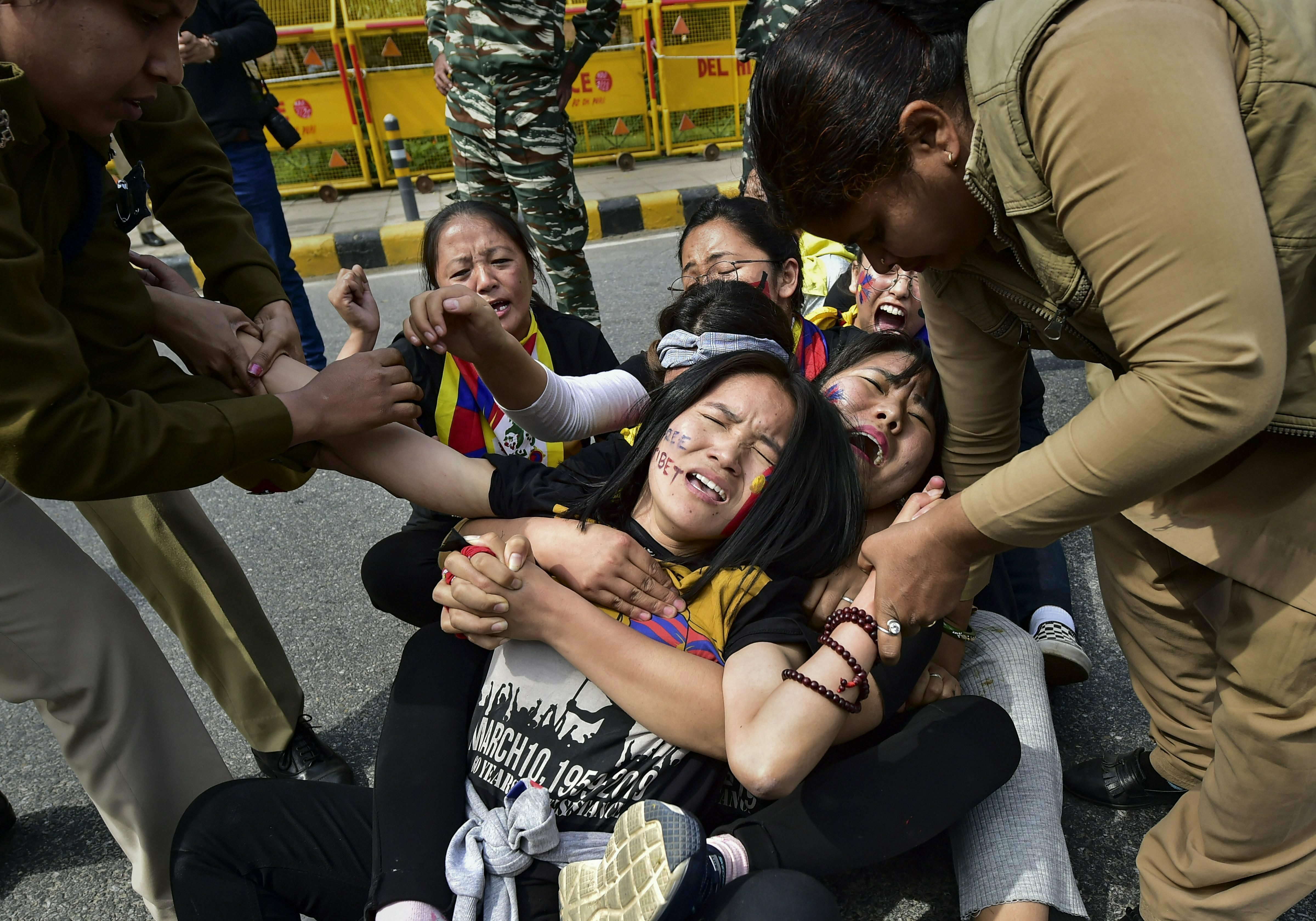 Police personnel detain Tibetan activists during their protest to commemorate the anniversary of 1959 Tibetan uprising against Chinese rule, near the Chinese embassy in New Delhi - PTI
