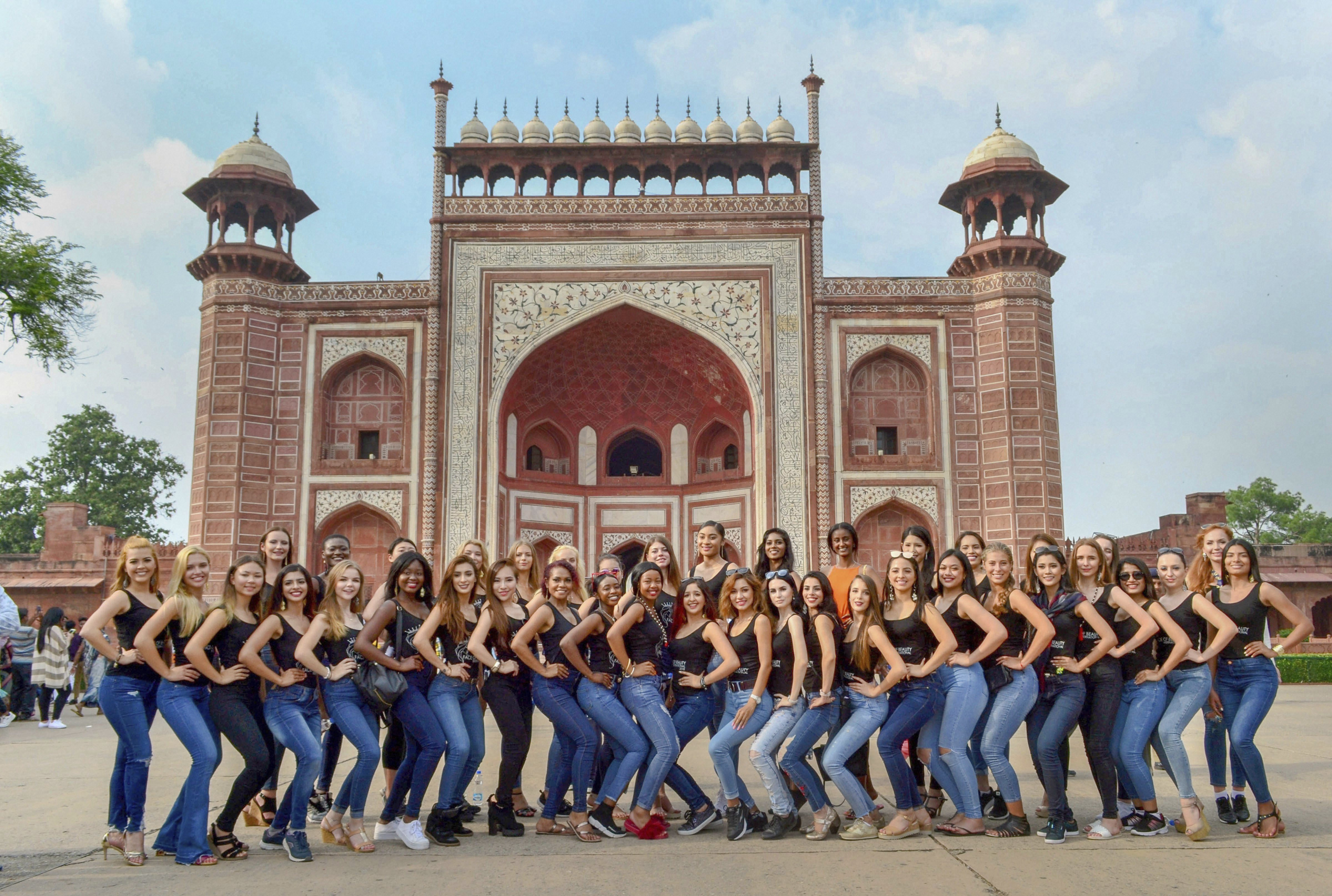 Models participating in an international beauty pageant pose for photos at the Taj Mahal premises, in Agra - PTI