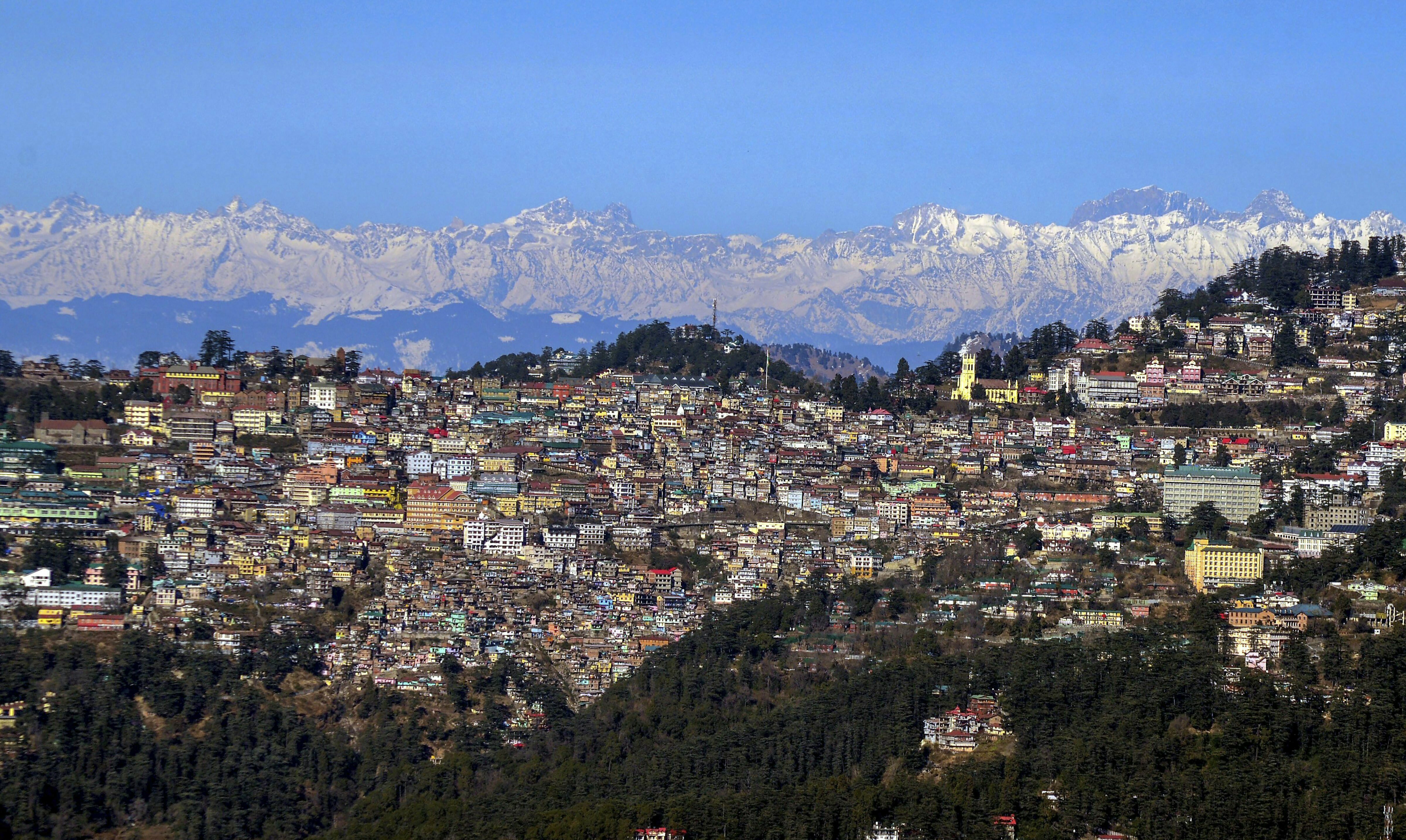A view of the hill city of Shimla seen in the backdrop of snow covered mountains - PTI