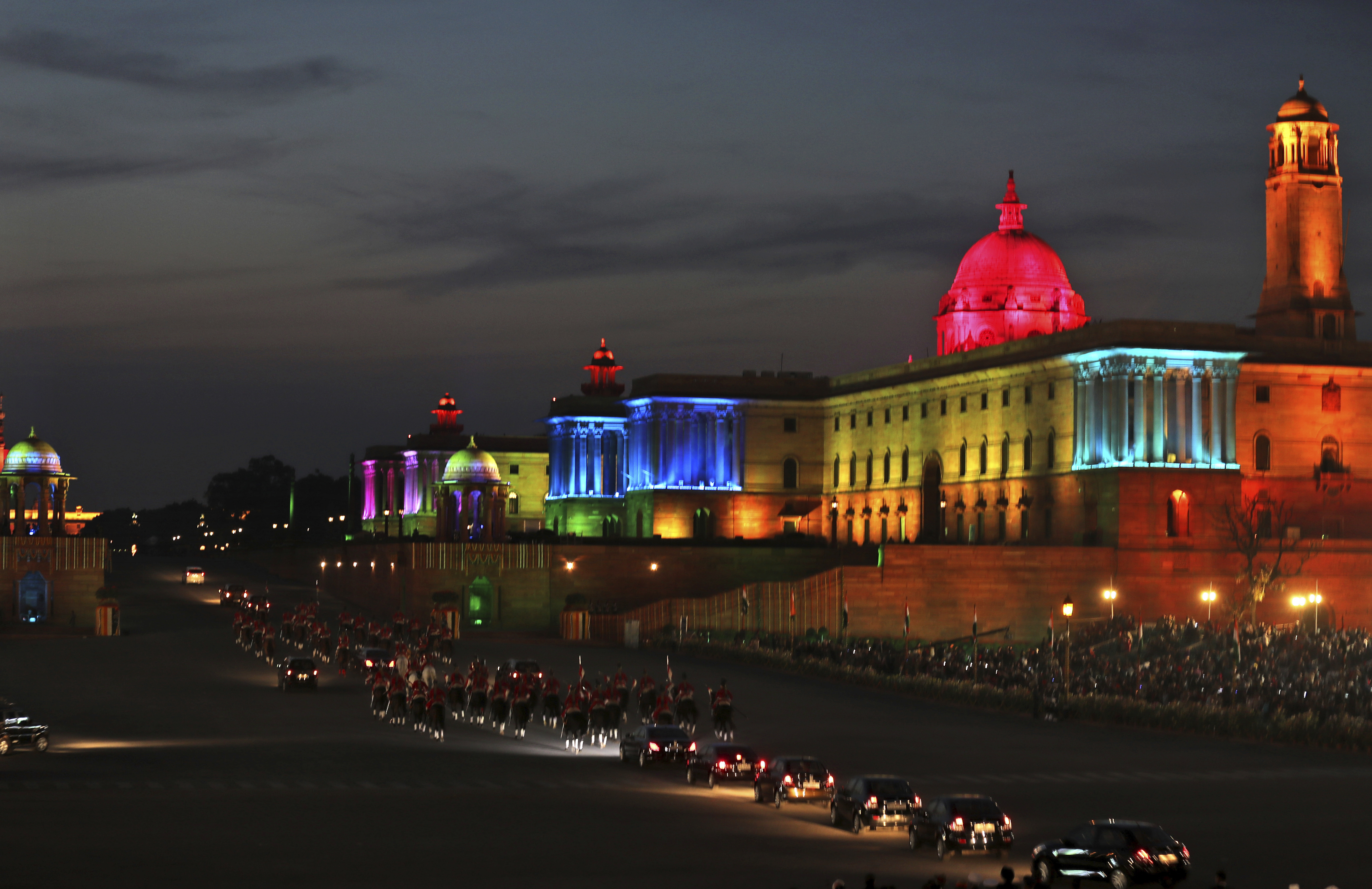 The Indian President's cavalcade leave escorted by horse-mounted presidential bodyguards, past the illuminated north and south blocks, the government seat of power, at the end of the Beating Retreat ceremony at Raisina Hills, in New Delhi, India - AP