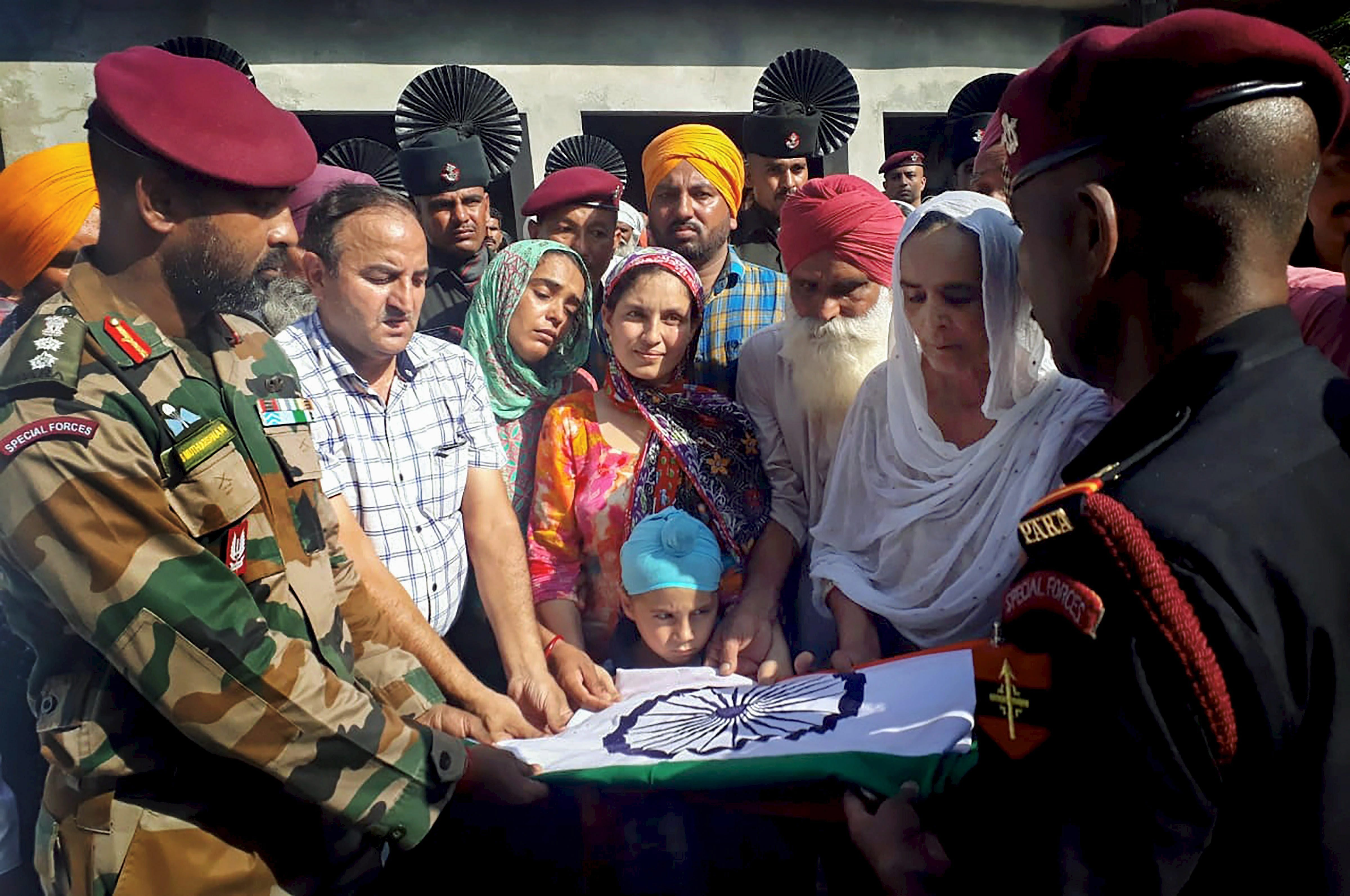 Army officers present the national flag that was wrapped around the body of Lance Naik Sandeep Singh to his family members, after his cremation at Kotla Khurd in Gurdaspur, Punjab - PTI
