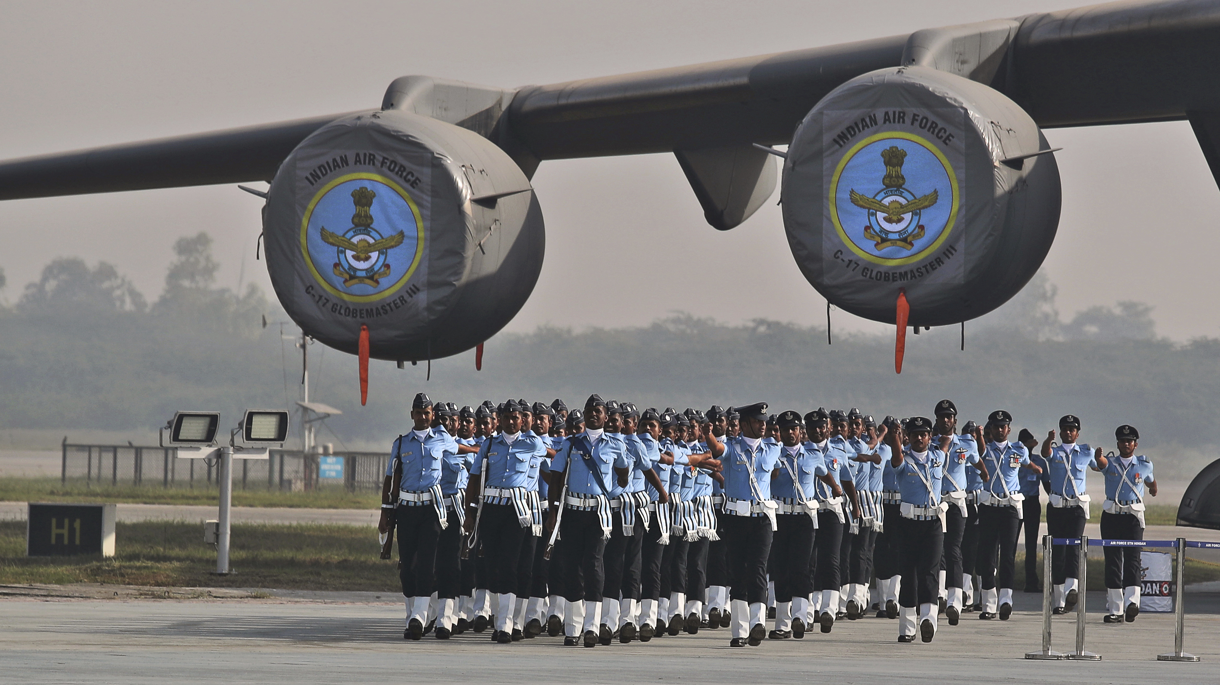 Indian Air Force soldiers march past their C-17 Globemaster military transport aircraft during the Indian Air Force day parade at the Hindon air base on the outskirts of New Delhi - AP