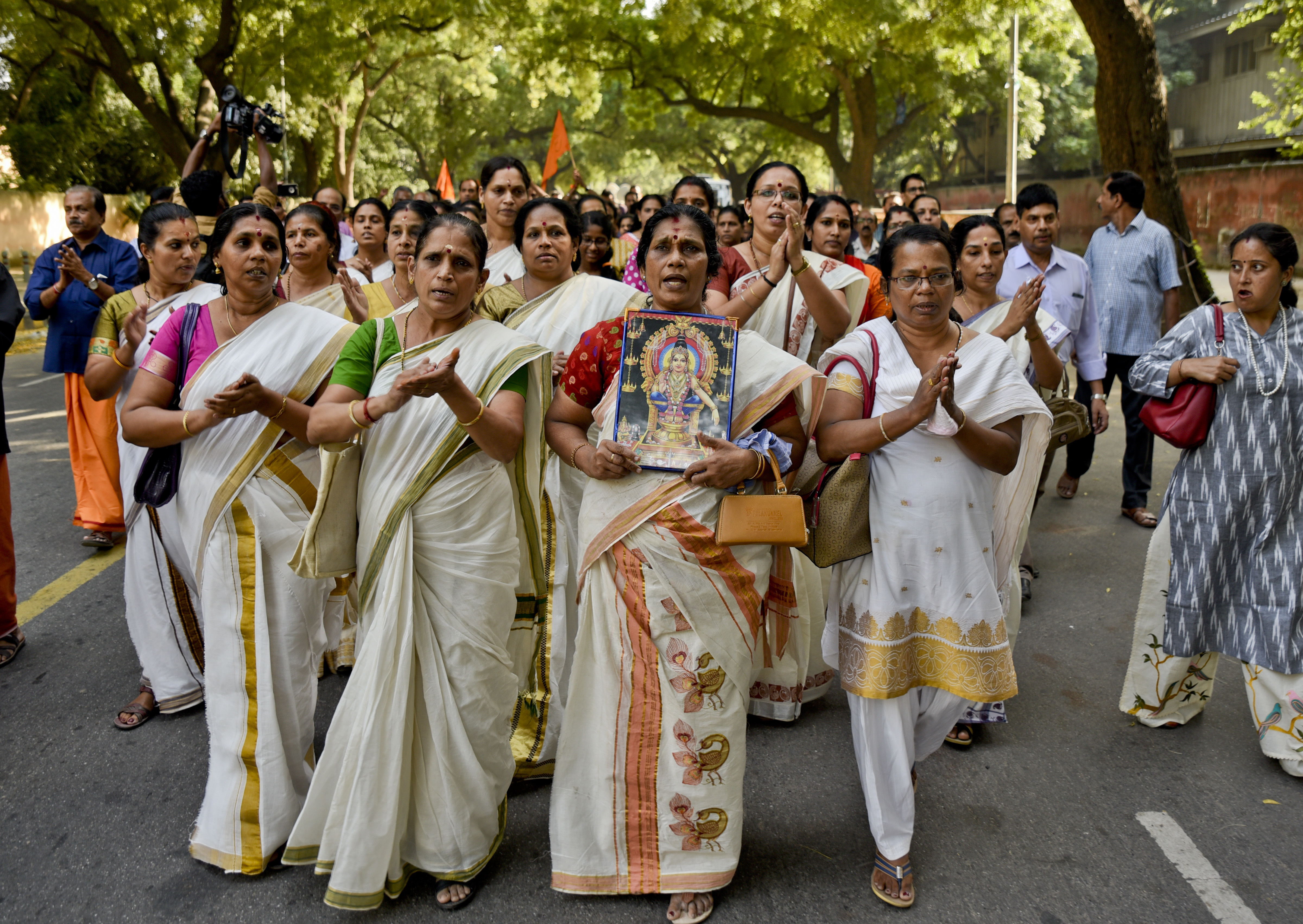 Indian Hindu women chant religious hymns worshipping Lord Ayyappa, the deity of Sabarimala temple, as they arrive for a protest against a recent Supreme Court verdict in New Delhi - AP