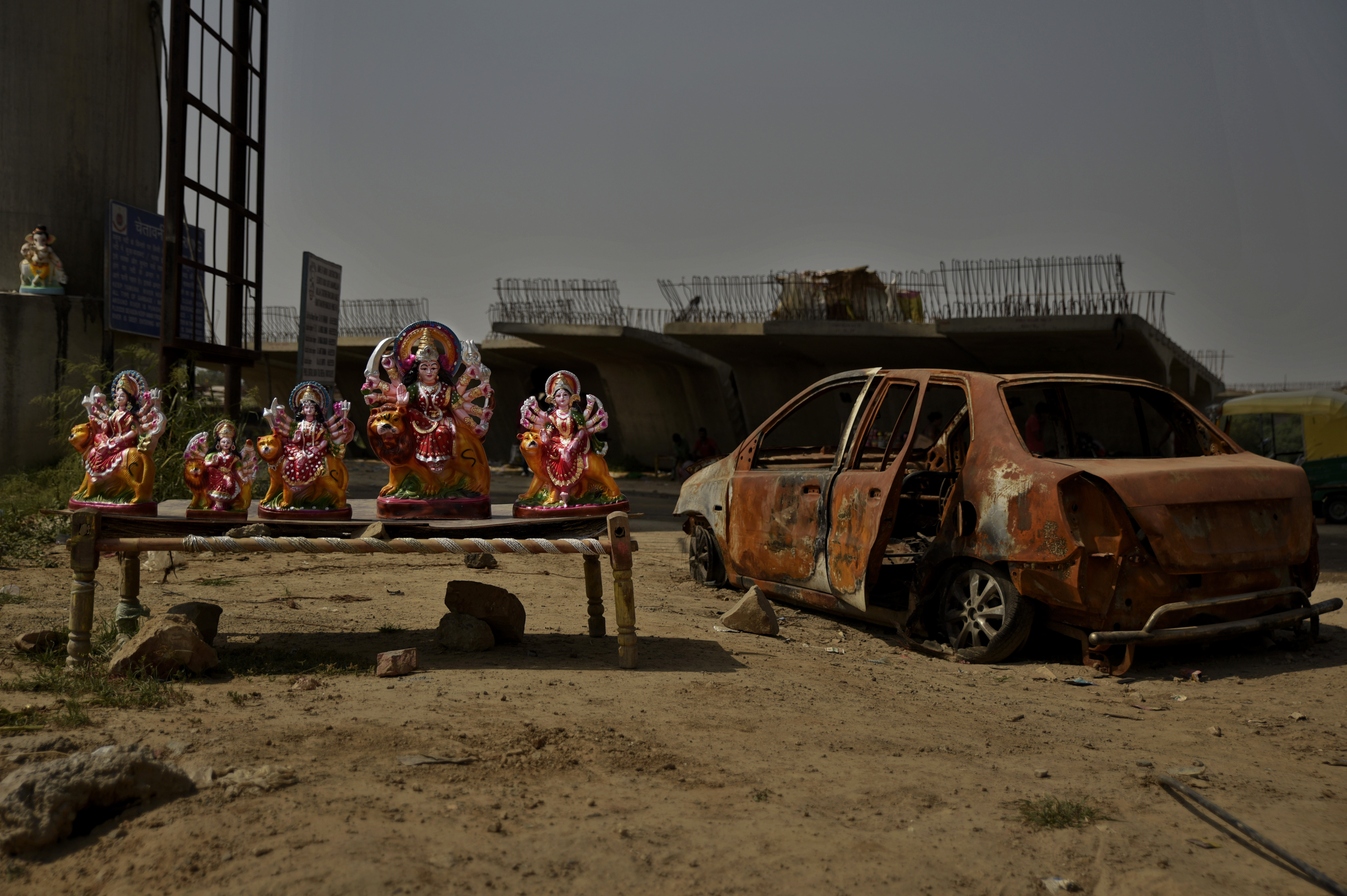 Idols of Hindu goddess Durga are displayed for sale on a roadside next to the remains of a damaged car in New Delhi - AP
