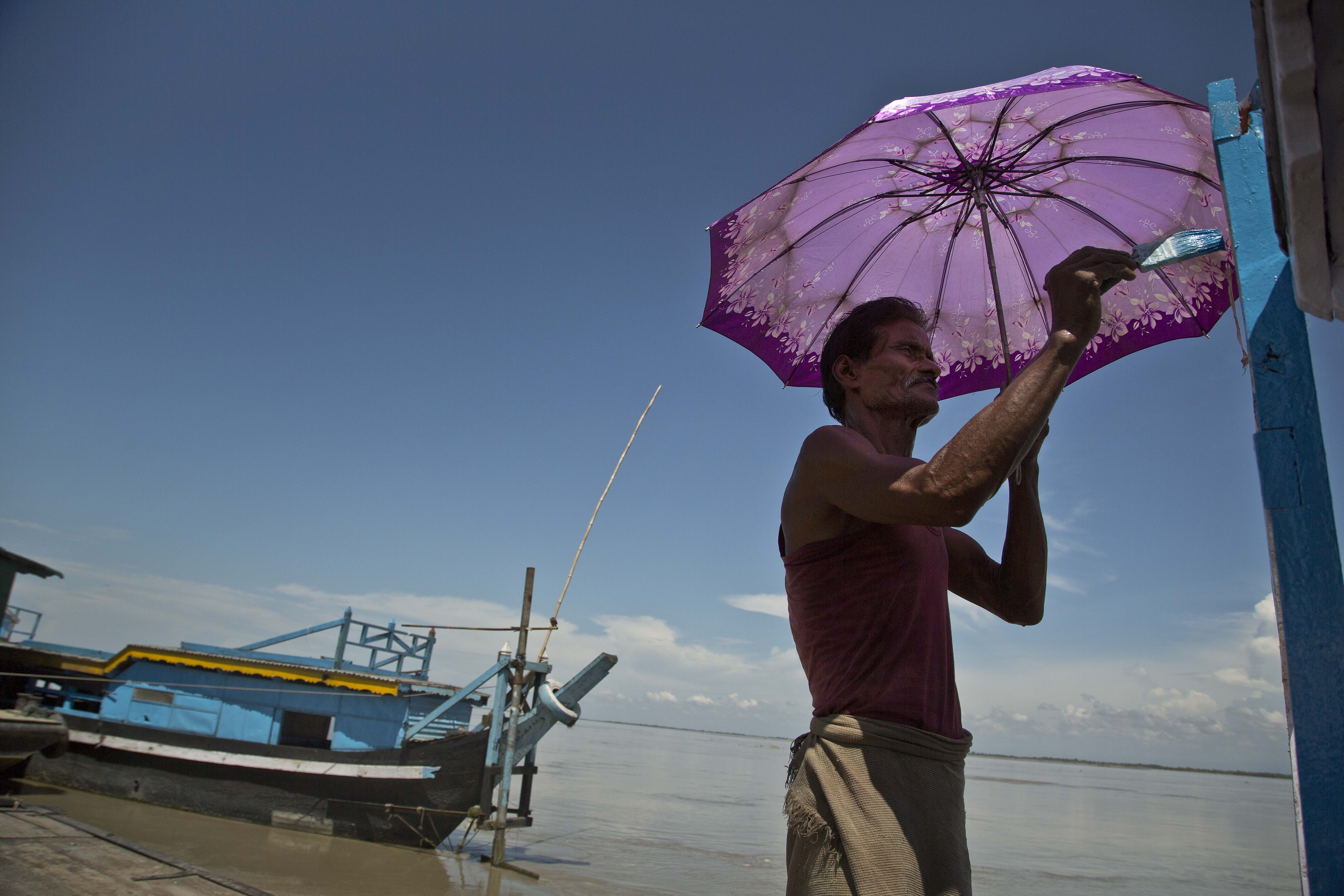 Betharam paints his boat on the bank of river Brahmaputra in Majuli - AP