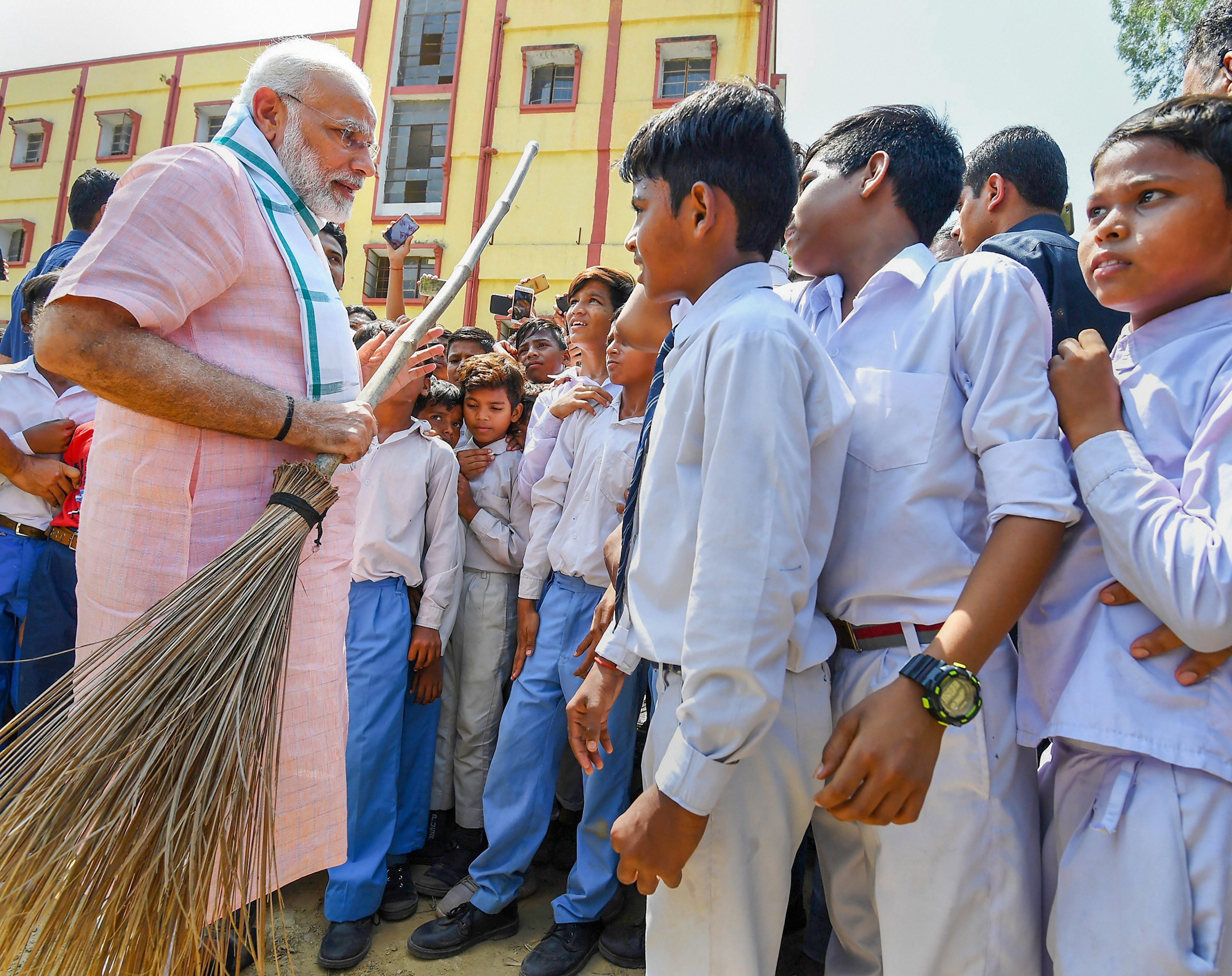 Prime Minister Narendra Modi interacts with the student as he undertakes a cleanliness drive under 'Swachhta Hi Sewa' campaign in the premises of Baba Sahib Ambedkar Higher Secondary School at Paharganj - PTI