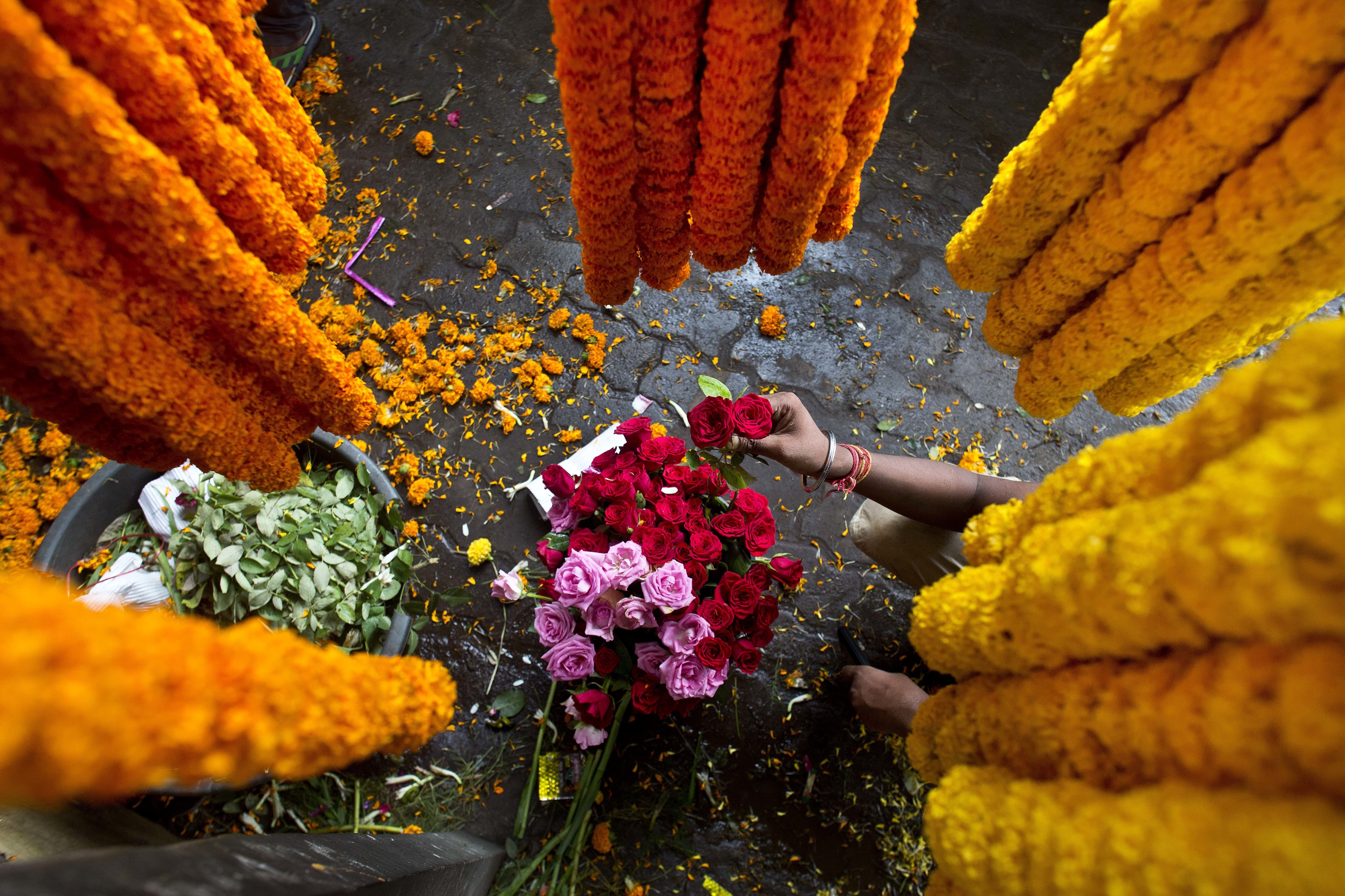 An Indian vendor arranges flowers surrounded by strings of marigold in Gauhati - AP
