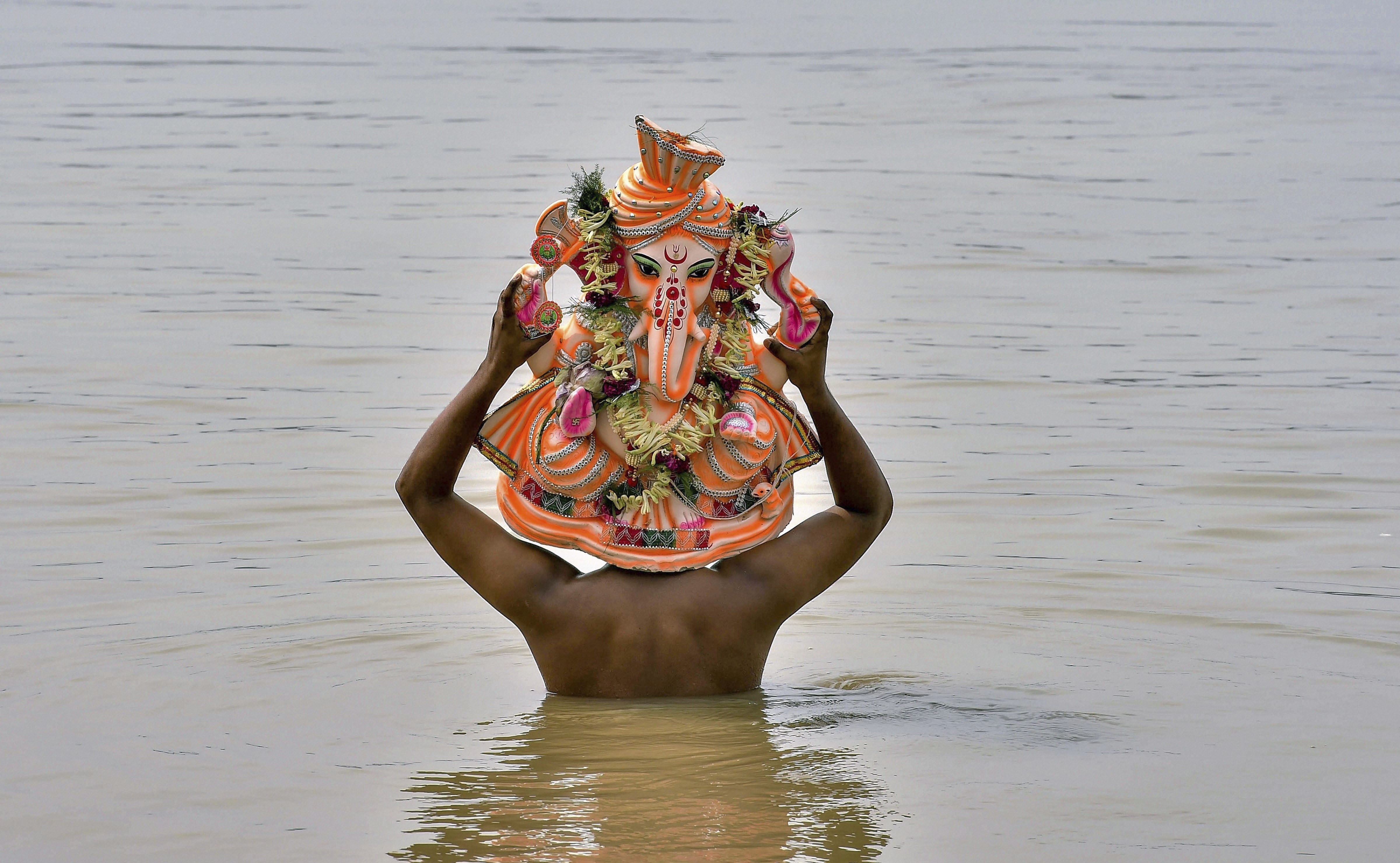 A devotee carries a clay idol of Lord Gamesh on his head to immerse in the Ganga River a day after Ganesh Chaturthi celebrations, in Kolkata - PTI