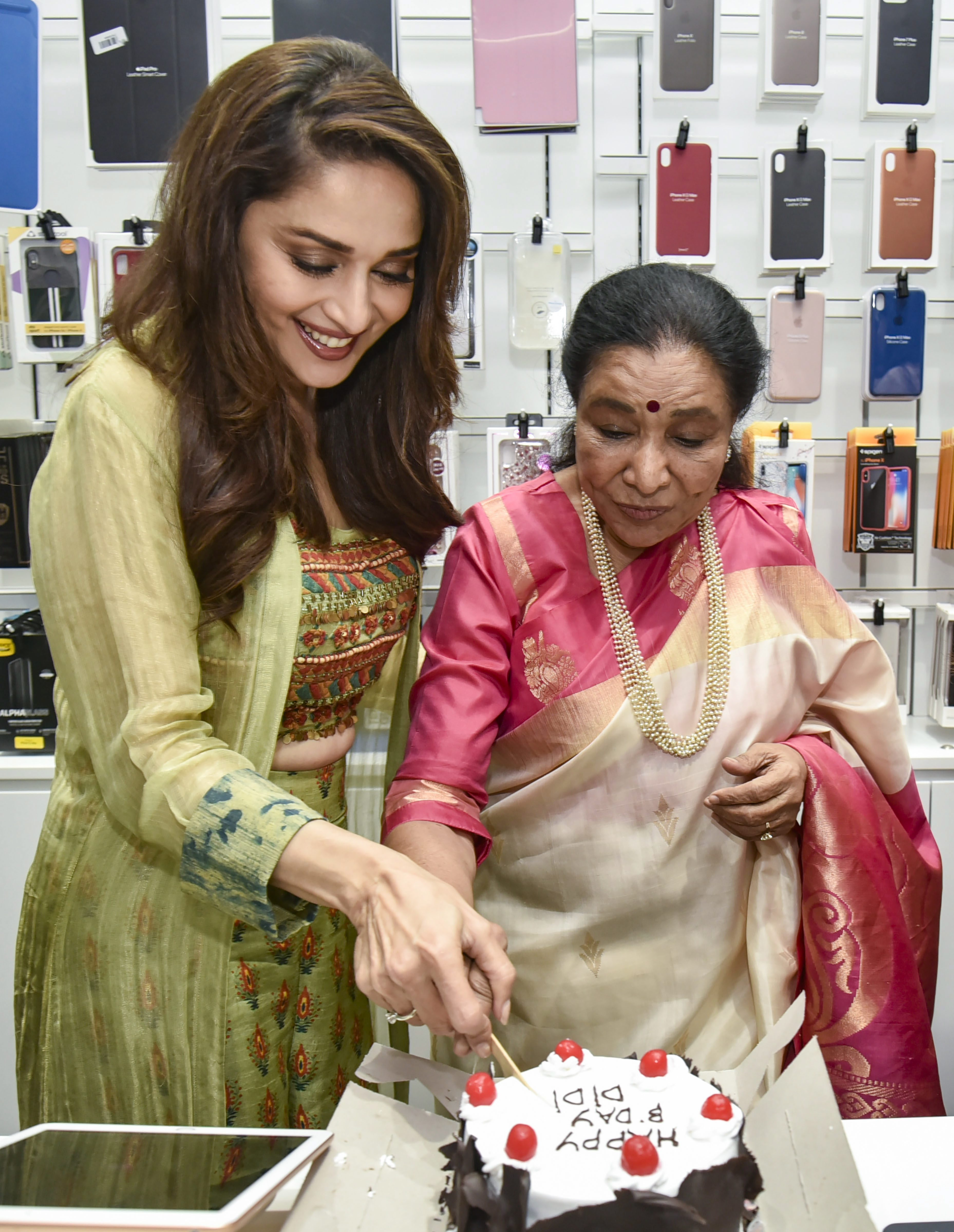 Bollywood singer Asha Bhosle with actor Madhuri Dixit Nene cut a cake during a product promotion, in Mumbai - PTI