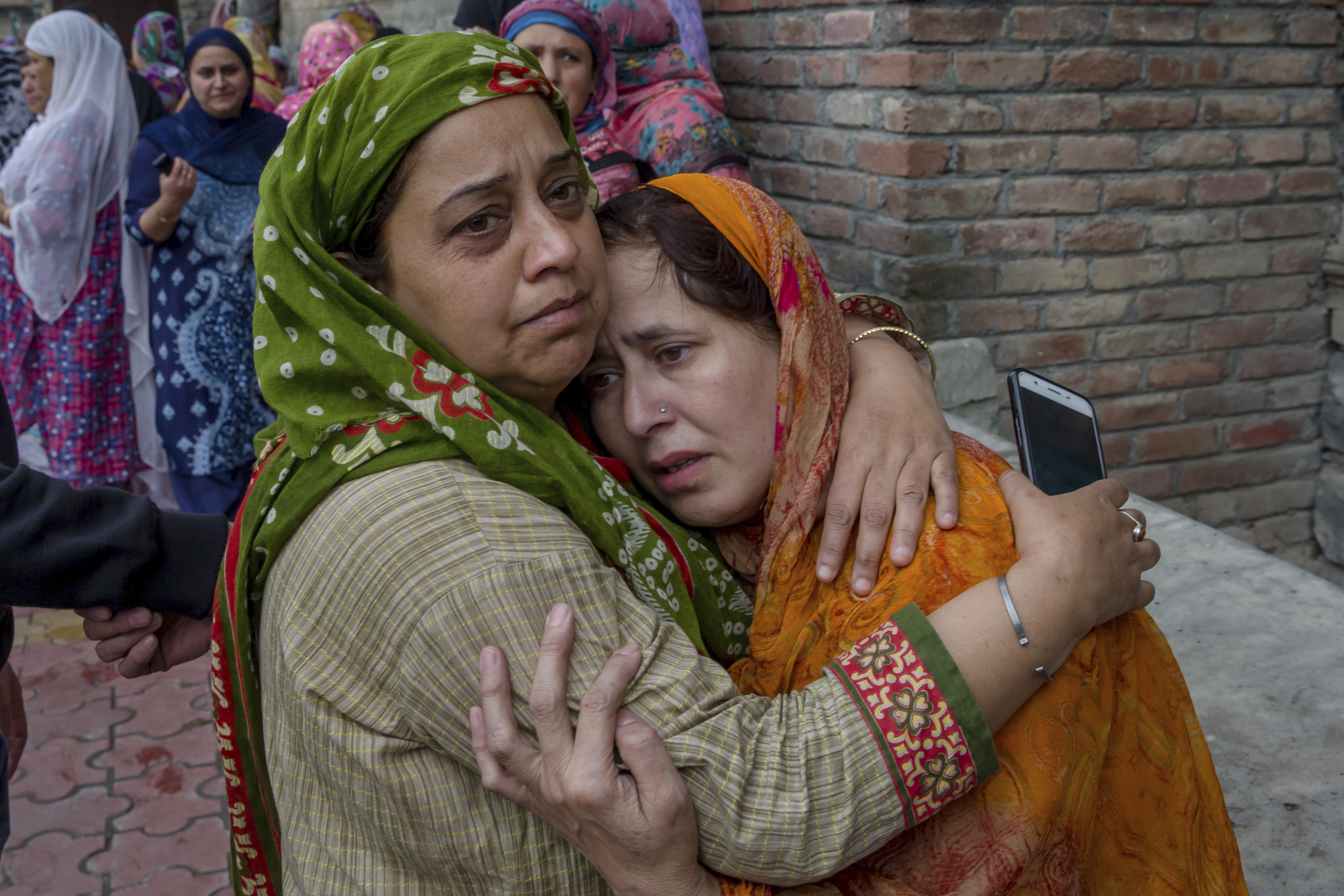 An unidentified woman comforts the grieving relative of Nazir Ahmed Wani during his funeral in Srinagar - AP