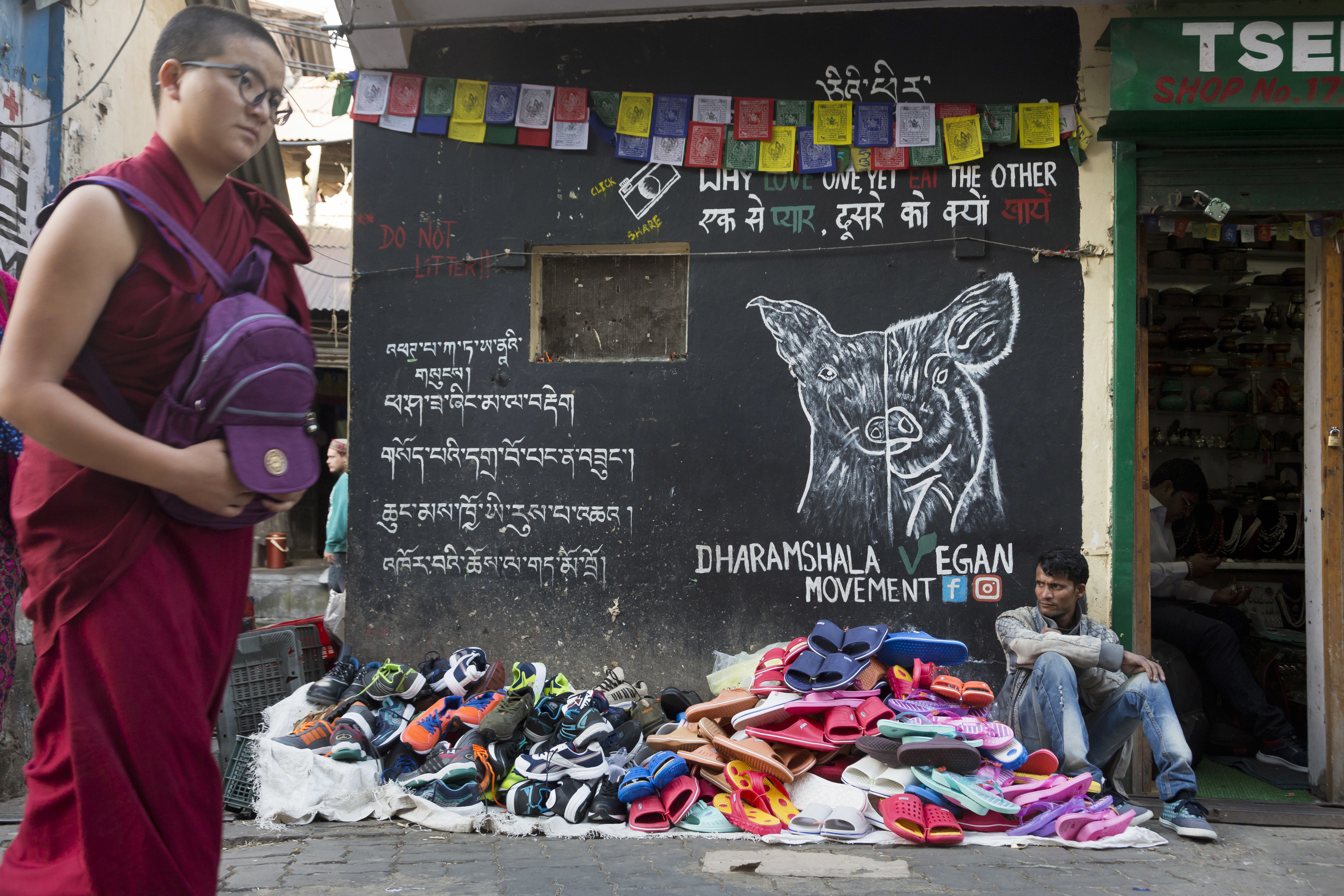 A man sells footwear in front of a wall painted with a message from a vegan society by a roadside in Dharmsala - AP