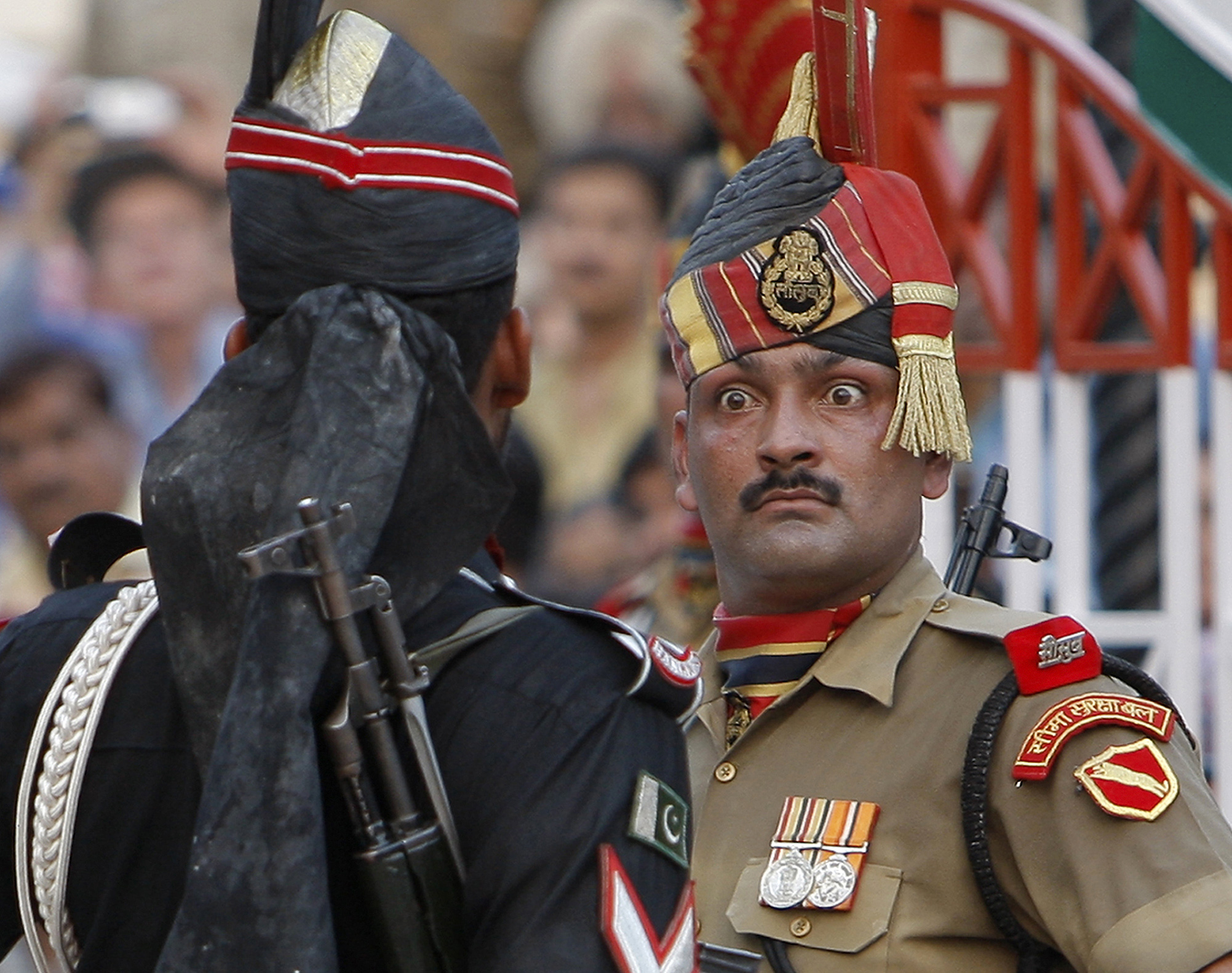 Indian Border Security Force soldier, right, and a Pakistani Rangers soldier face one another at a daily closing ceremony at the Wagah border post near Lahore - AP