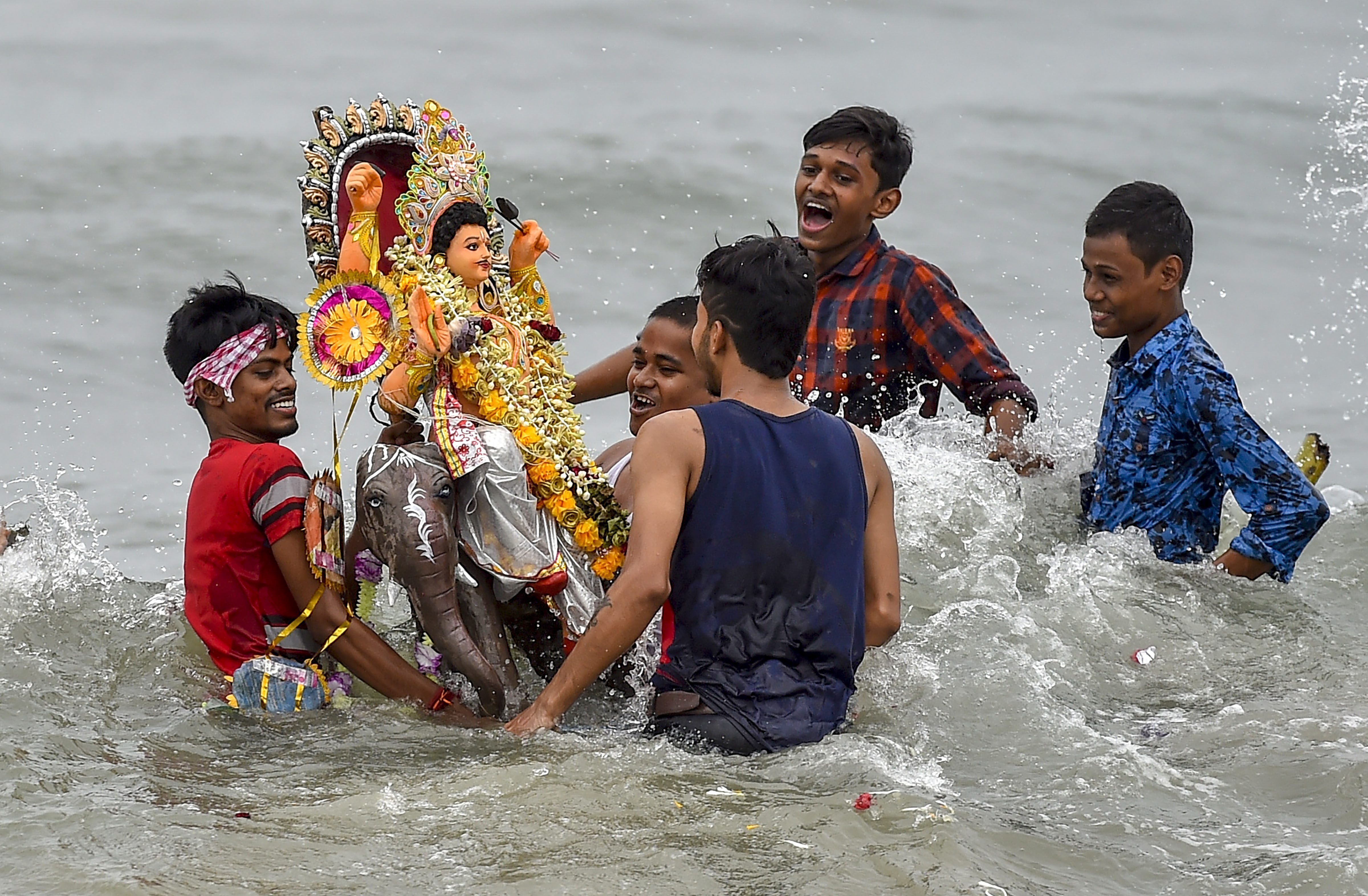 Devotees immerse an idol of Lord Vishwakarma at Bay of Bengal, in Chennai - PTI