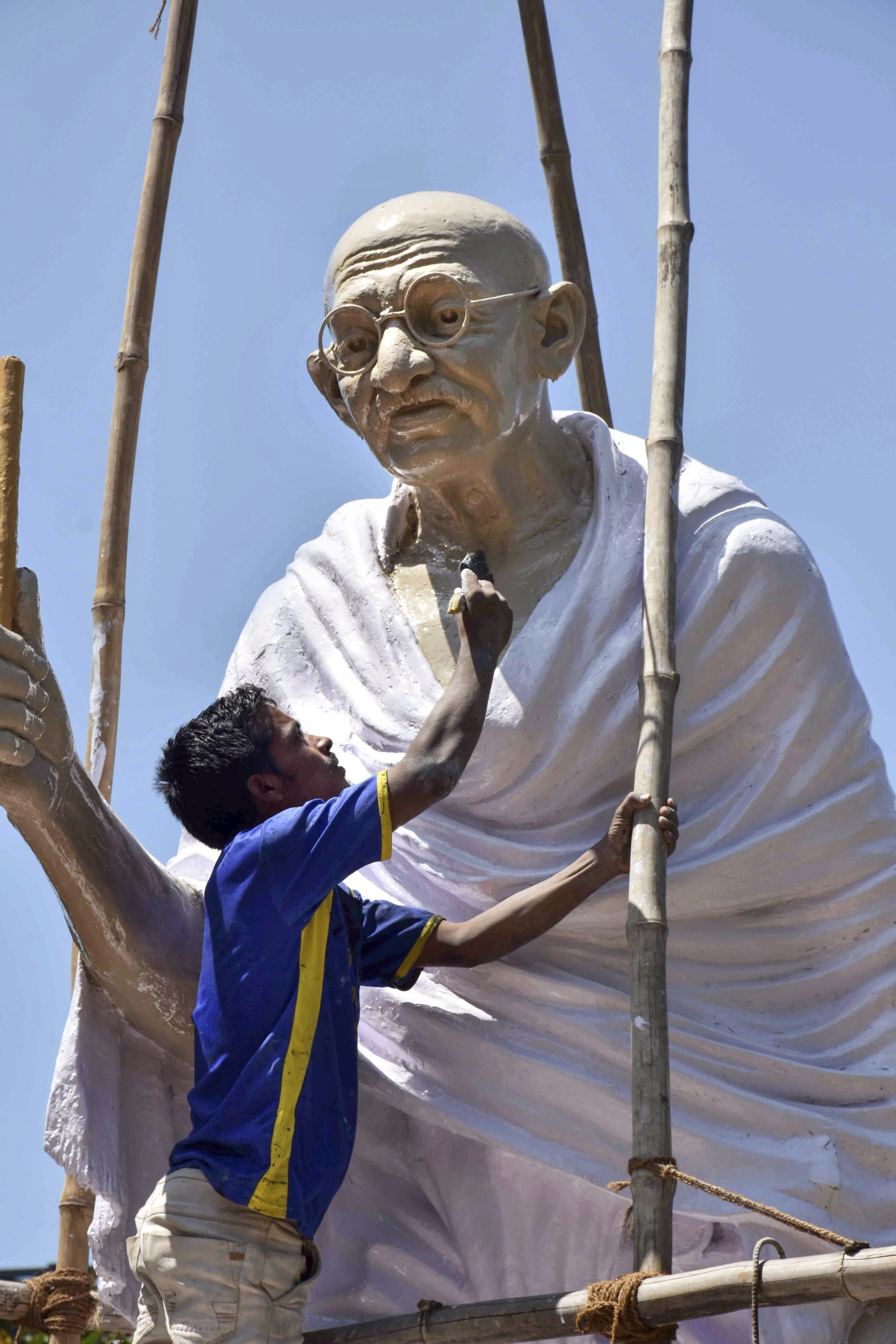 A worker cleans the statue of Mahatma Gandhi ahead of 'Gandhi Jayanti' at Mohrabadi Ground in Ranchi - PTI