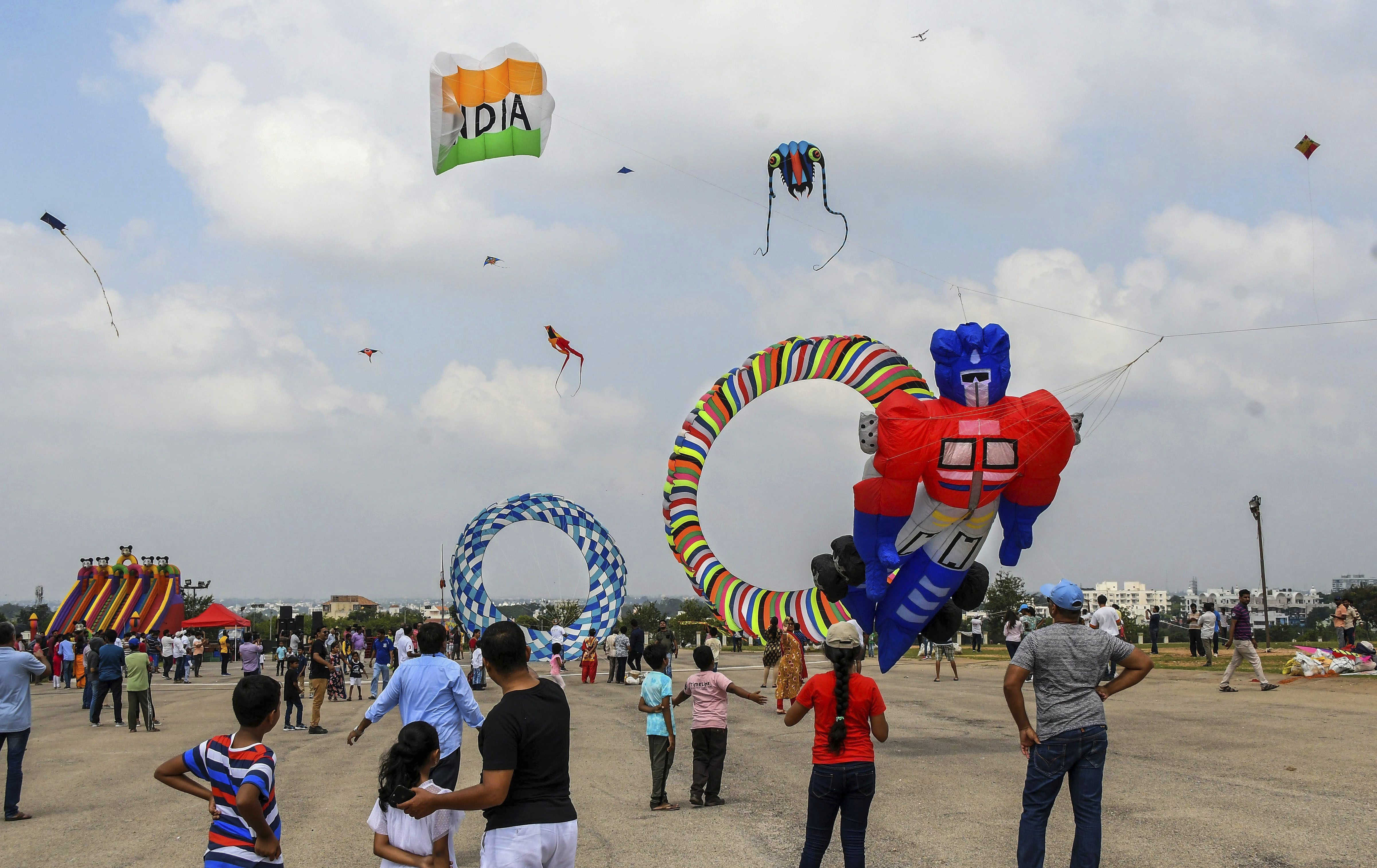 Enthusiasts fly kites of various shapes and sizes during a kite festival organised as part of Dussehra celebrations, at the foothills of Chamundi Hills in Mysuru - PTI