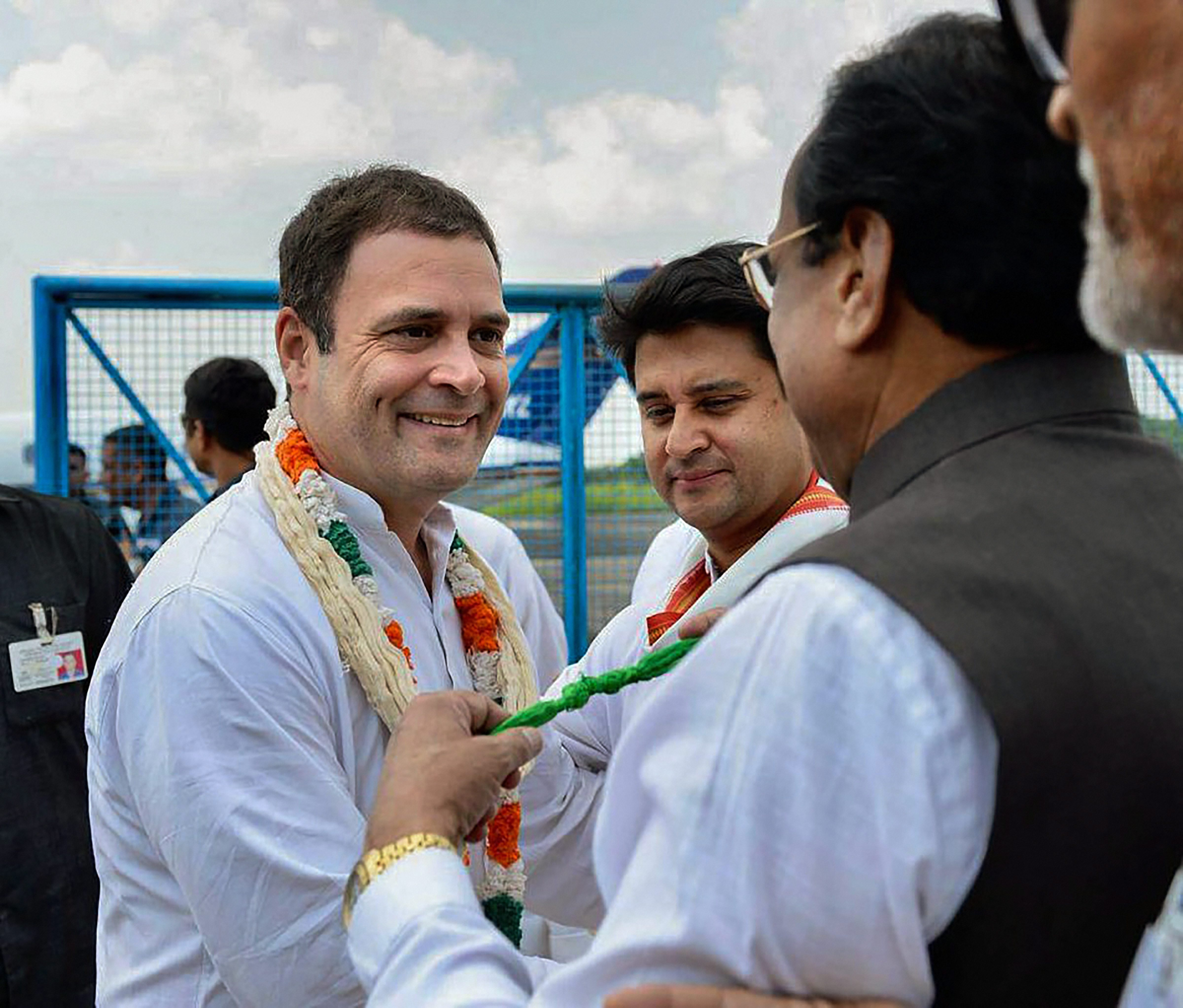 Congress President Rahul Gandhi is greeted by State President Kamal Nath as Congress leader and MP Jyotiraditya Madhavrao Scindia looks on, at the airport ahead of a roadshow, in Bhopal - PTI