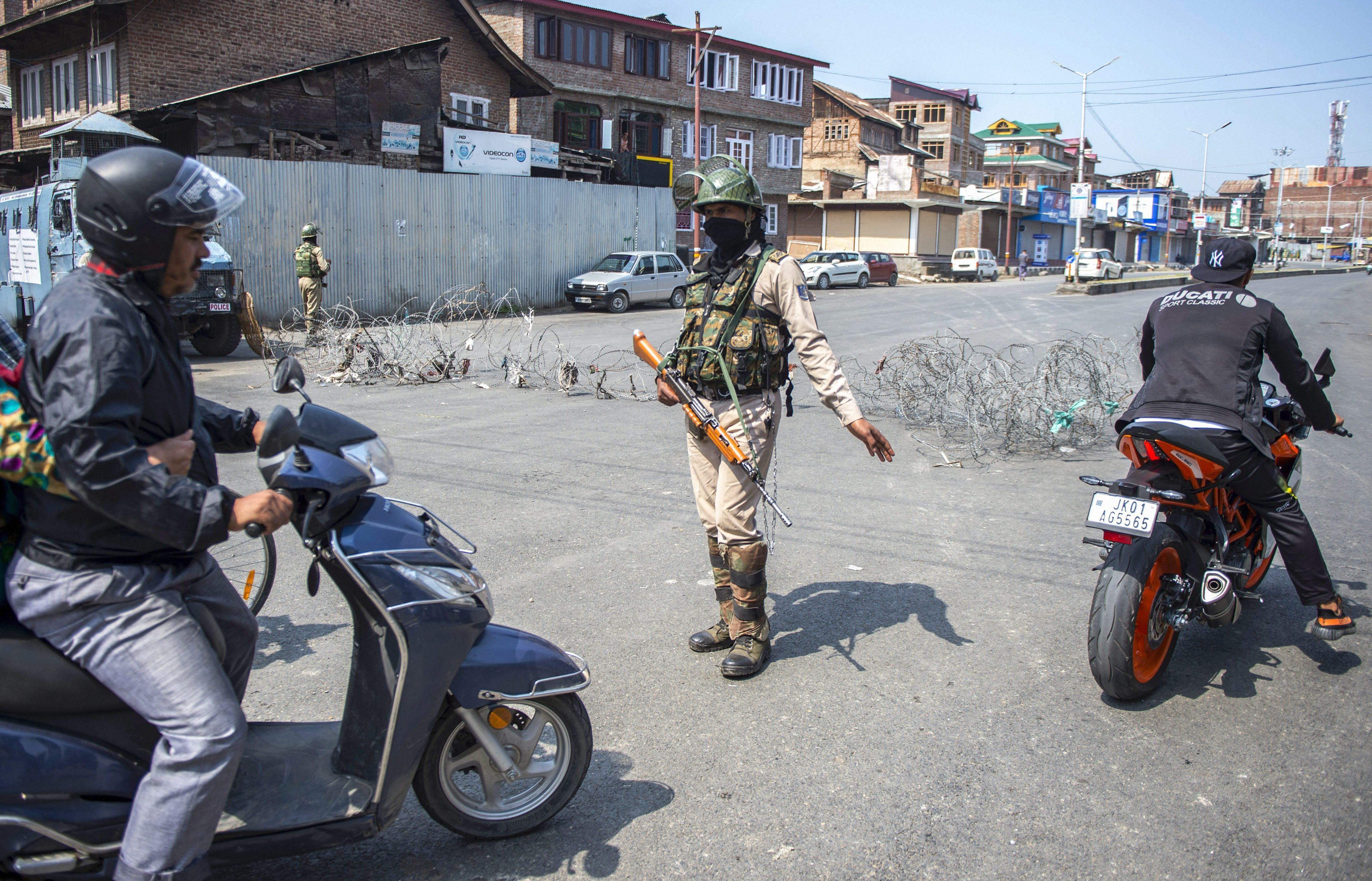 A security personnel stops a scooterist during a strike called by separatist leaders against the recent civilian and militant killings in south Kashmir, in Srinagar - PTI