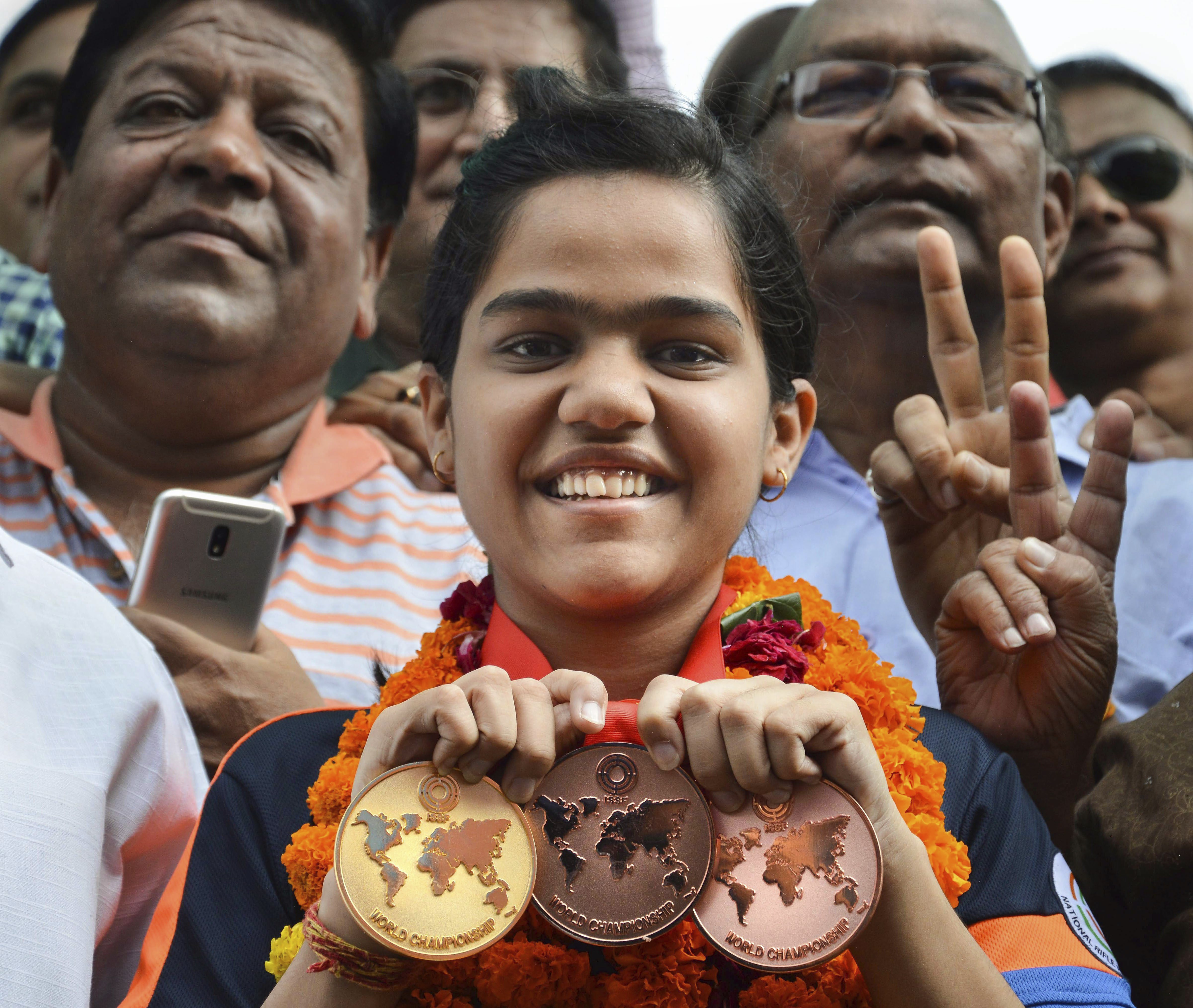 Gold medalist in shooting, Shreya Agarwal poses with her medals on her arrival at a railway station, in Jabalpur - PTI