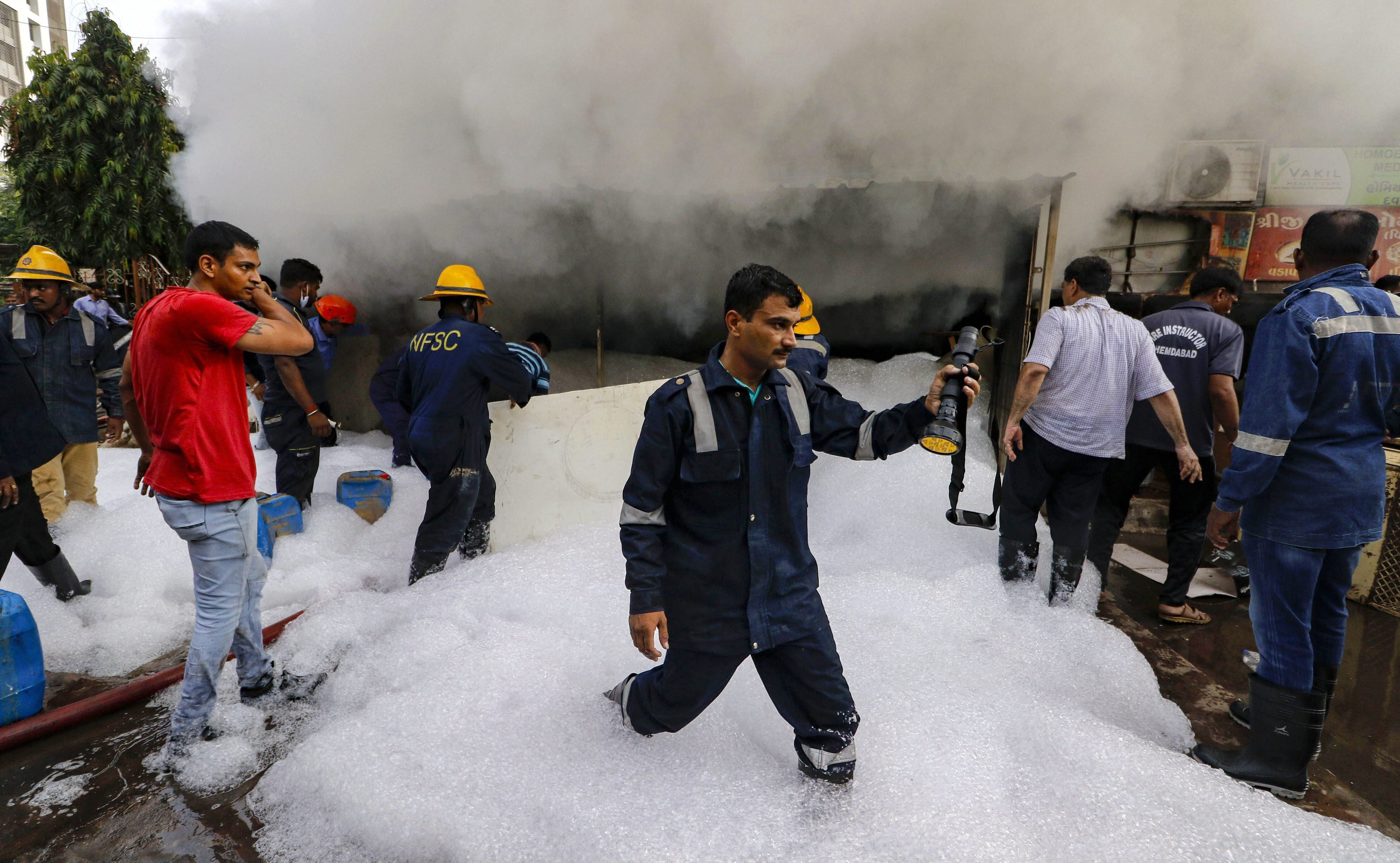 Firefighters try to control a fire which broke out in a tyre showroom, in Ahmedabad - PTI