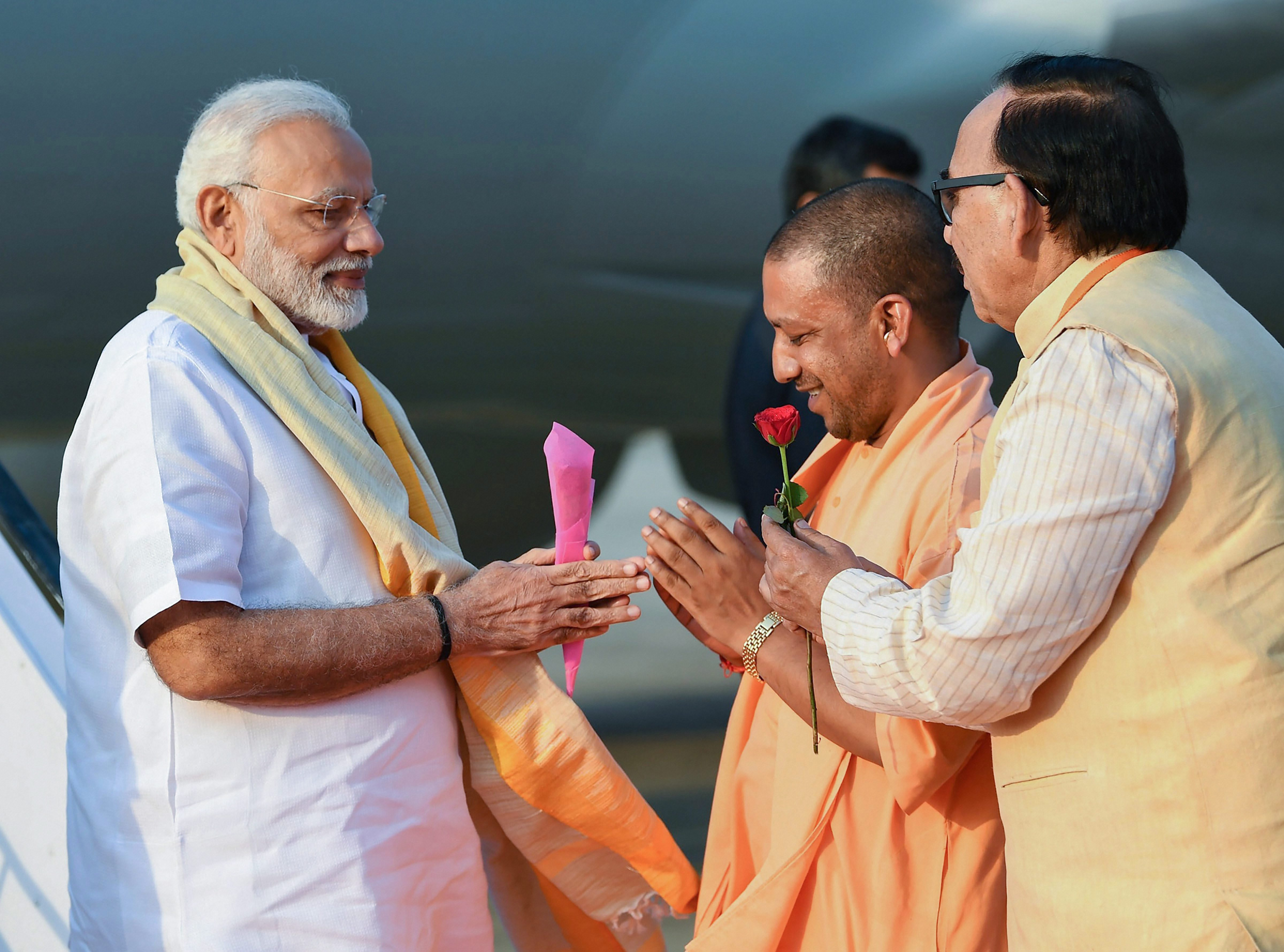 rime Minister Narendra Modi being welcomed by the Chief Minister of Uttar Pradesh Yogi Adityanath, on his arrival in Varanasi - PTI