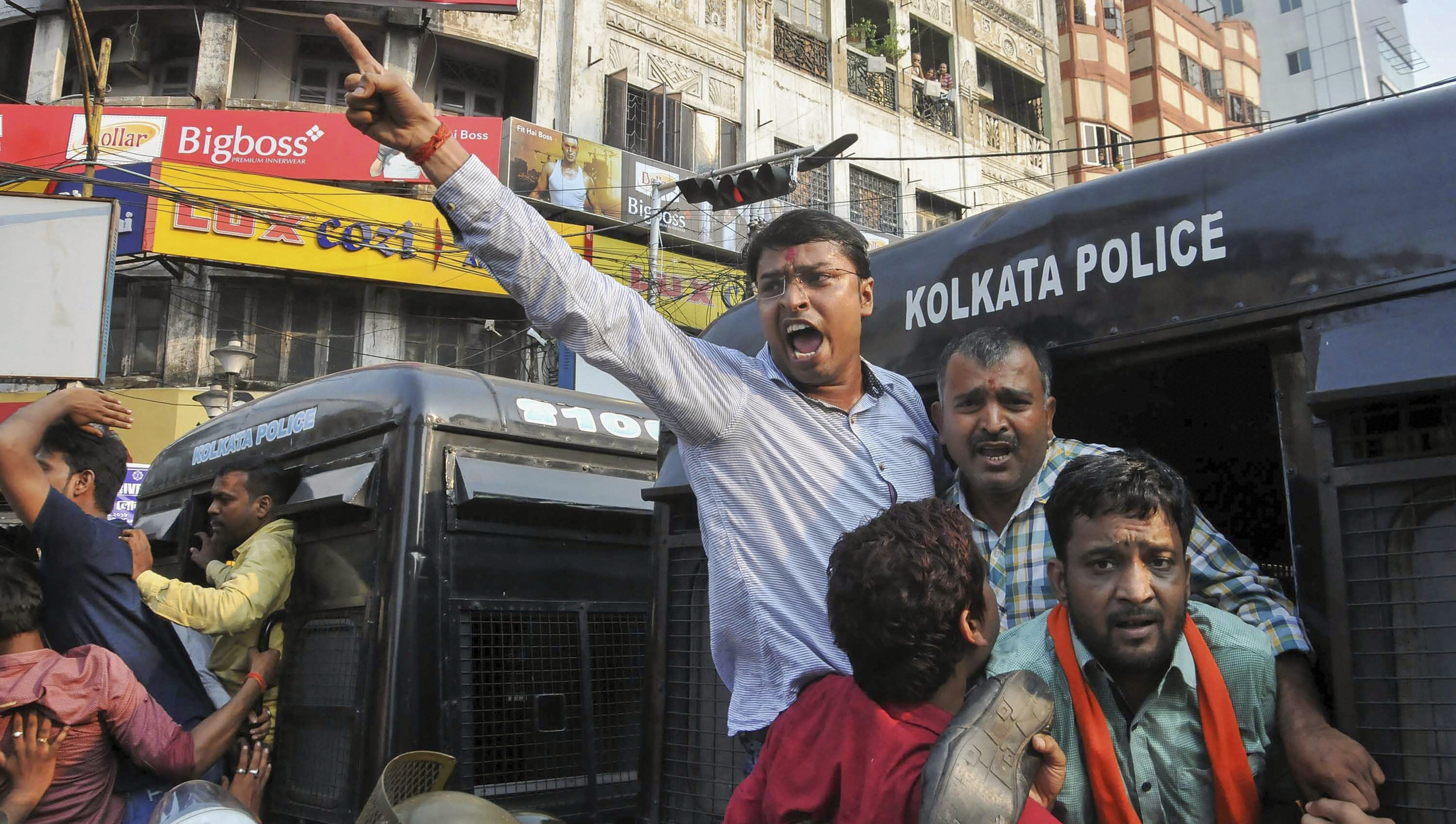 Police detain members of Bharatiya Janata Yuva Morcha (BJYM) during their road blockade agitation against the alleged attack on BJP West Bengal President Dilip Ghosh by Trinamool Congress workers in East Midnapore district of the state, in Kolkata - PTI