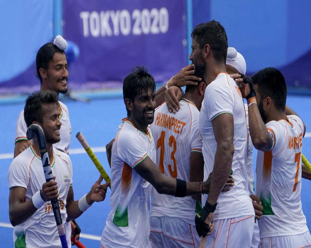 India's Harmanpreet Singh (13) celebrates with his teammates after scoring on Argentina goalkeeper Juan Manuel Vivaldi during a men's field hockey match at the 2020 Summer Olympics