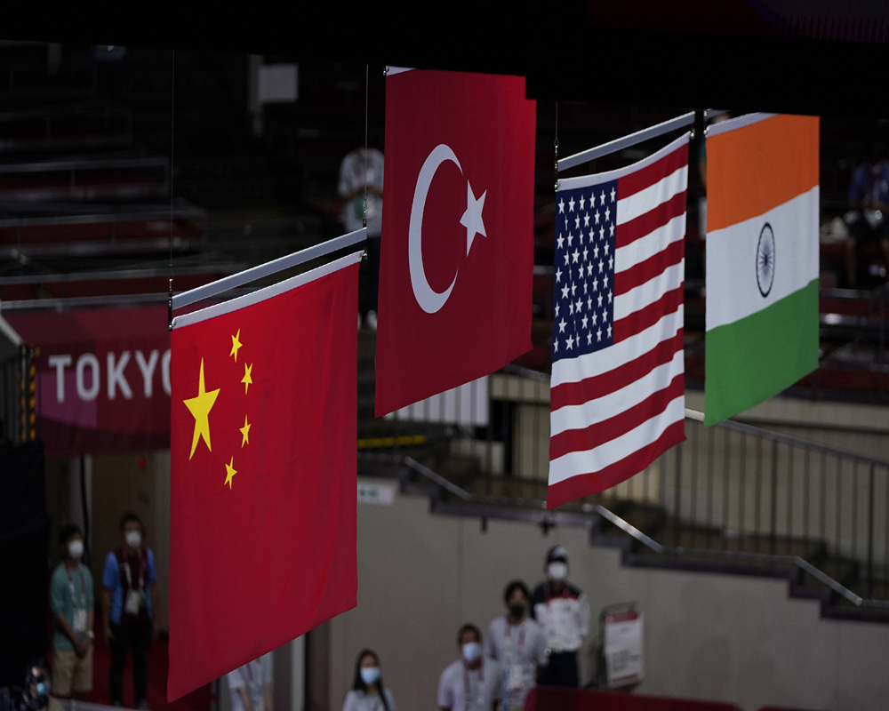 The national flags of medal winners Silver medal winner China's Cu Hong, left, gold medal winner Turkey's Busenaz Surmeneli, second from left, bronze medalist Oshae Jones, from the United States, third from left and bronze medalist India's Lovlina Borgohain, right, are raised during the women's welterweight 69-kg medal ceremony at the 2020 Summer Olympics