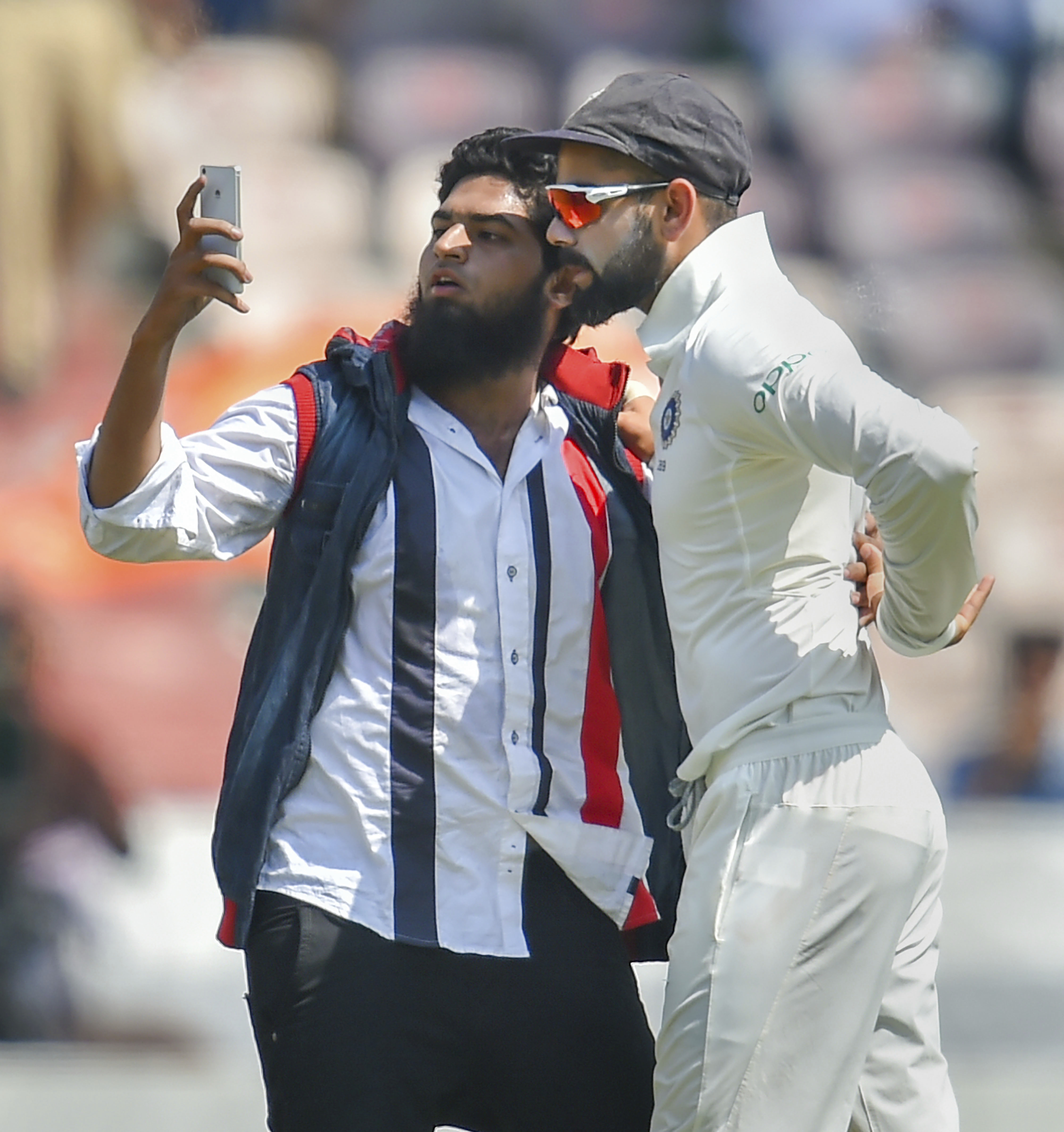 A pitch invader takes a selfie with Indian cricket captain Virat Kohli during the second test match between India and West Indies, in Hyderabad - AP