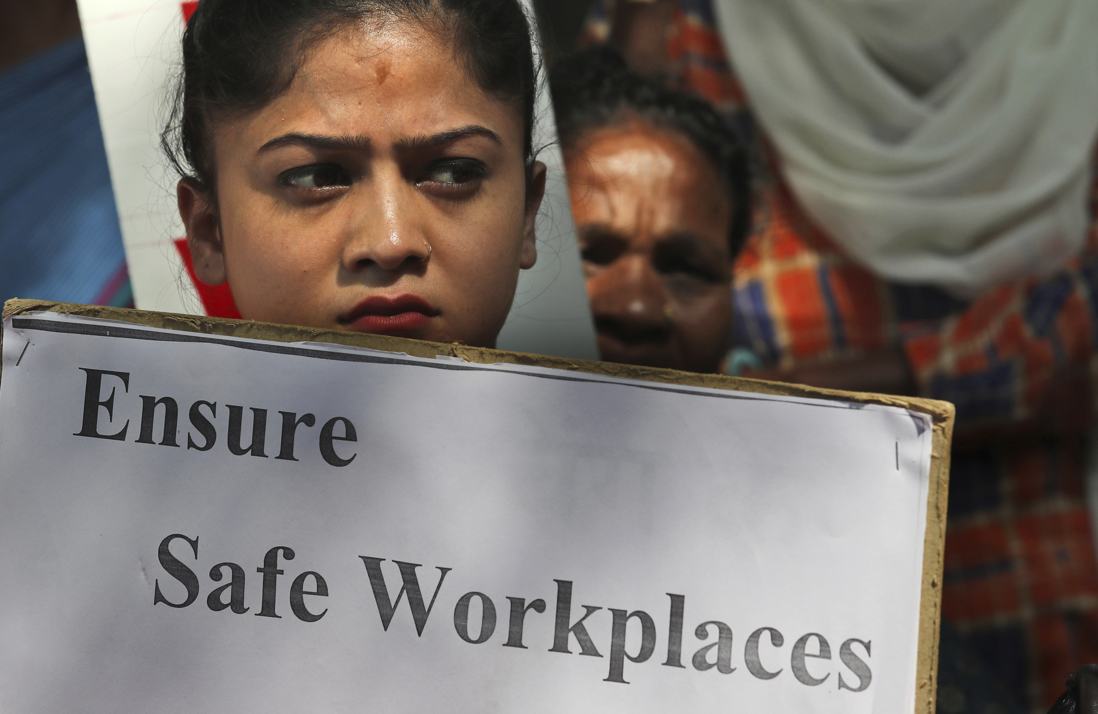 An Indian woman holds a banner during a protest against sexual harassment in the workplace in New Delhi - AP