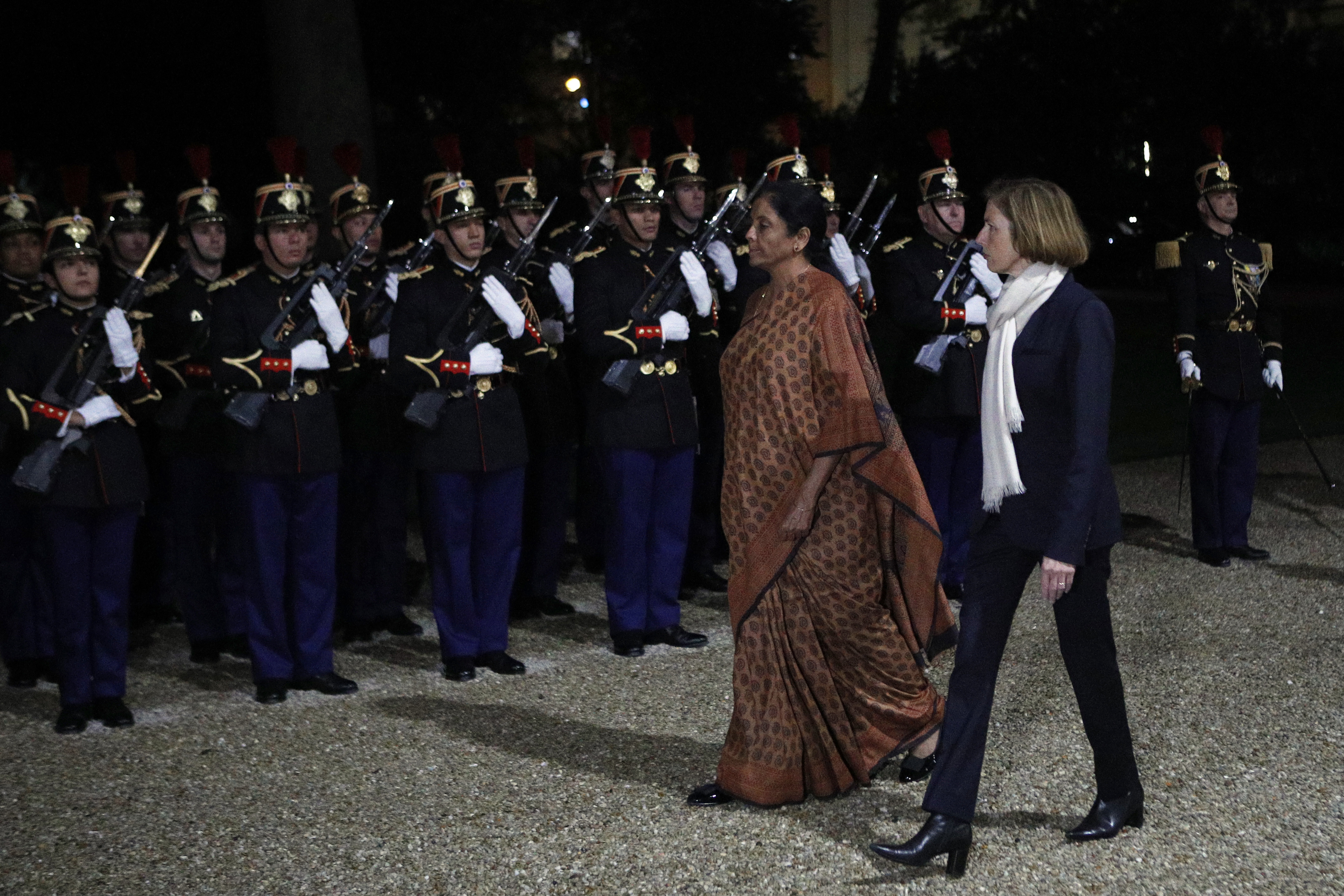 French defense minister Florence Parly, right, reviews French Republican Guards with India's defense minister Nirmala Sitharaman prior to their meeting at Hotel de Brienne Defense ministry in Paris - AP