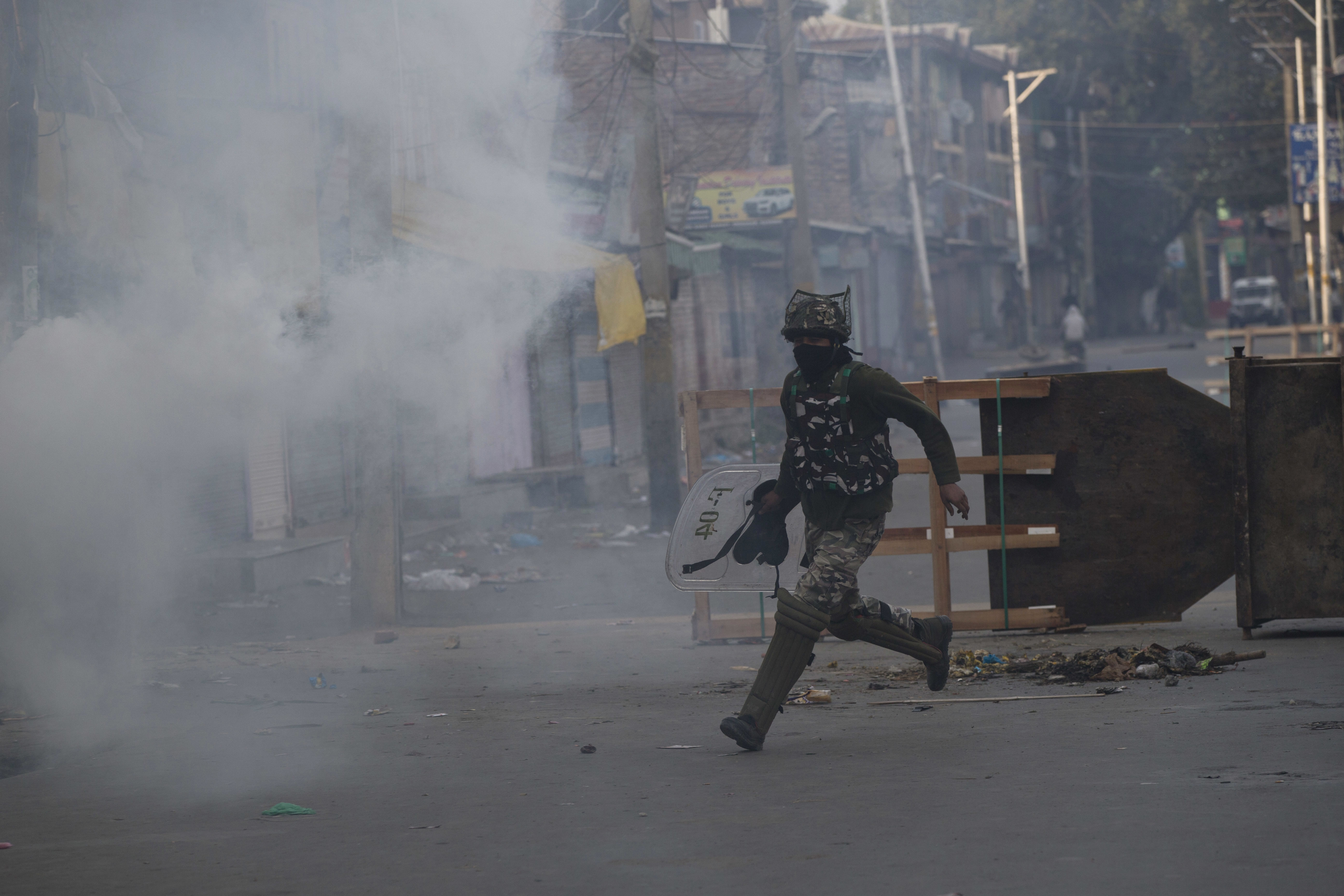 An Indian paramilitary soldier runs for cover during a protest in Srinagar - AP