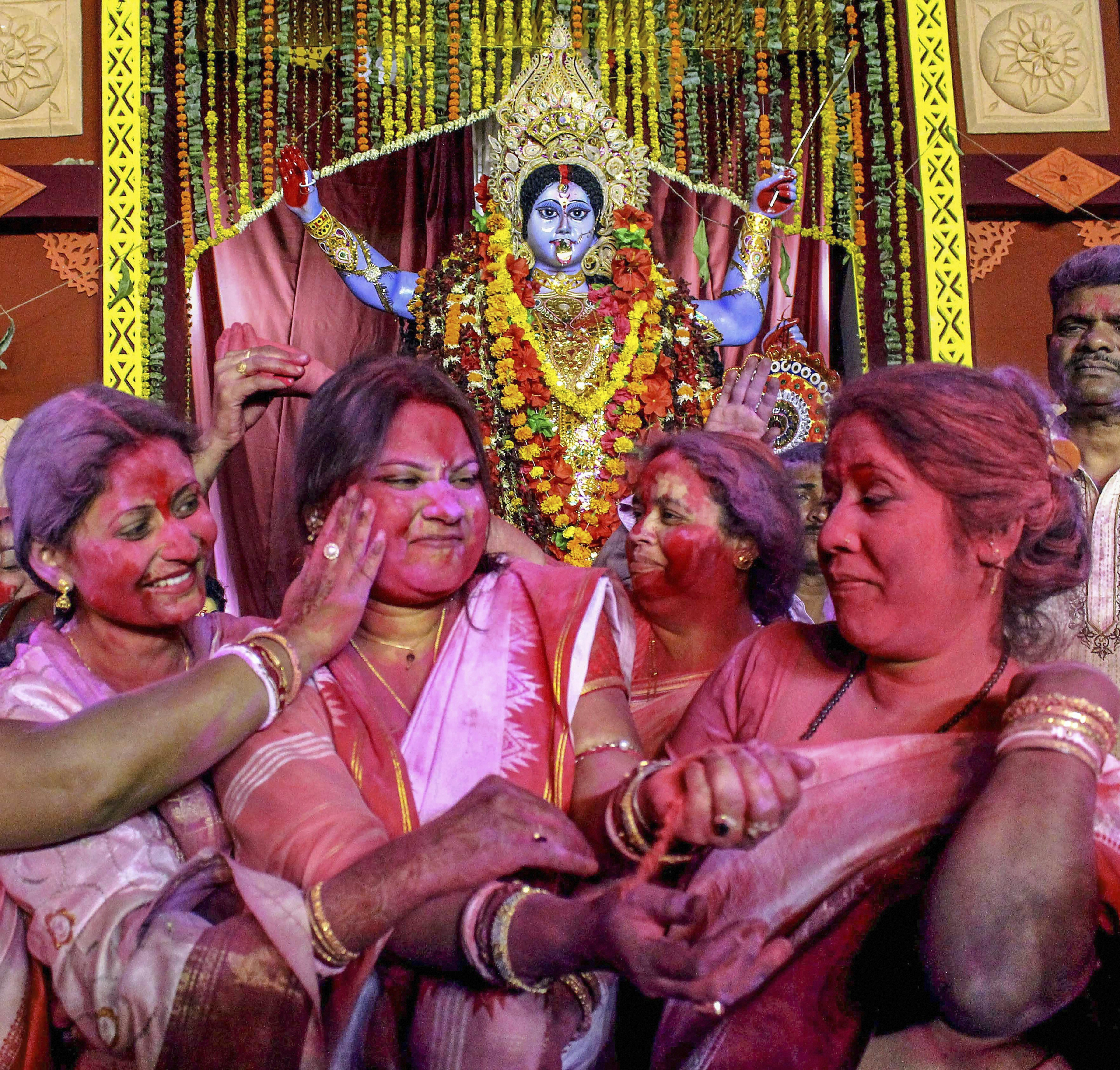 Women apply colour powder on each other's face ahead of 'Goddess Kali' idol immersion marking an end of Diwali festival, in Bhopal - PTI