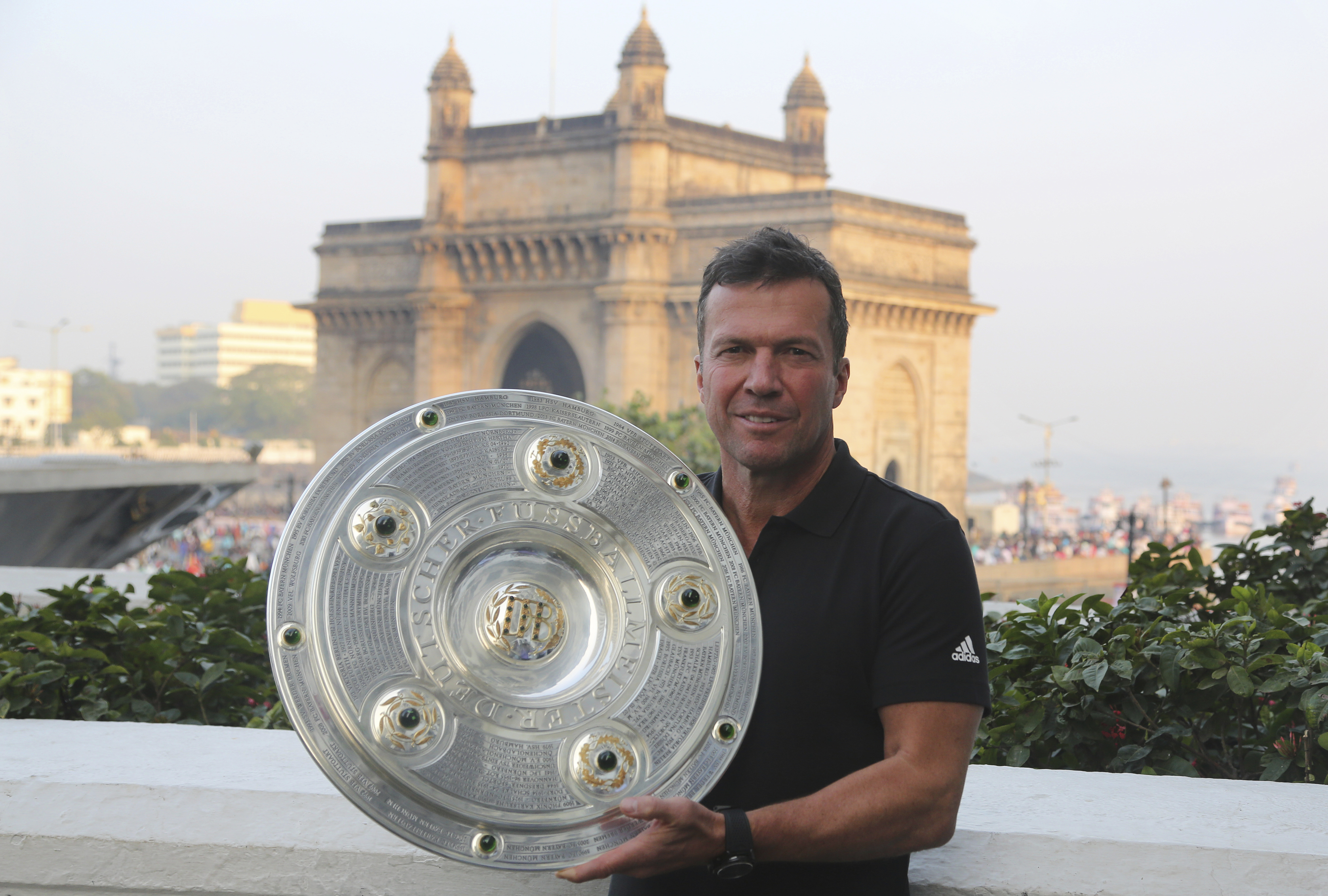 German Football player Lothar Matthaus poses for a photograph with Bundesliga trophy near the Gateway of India monument in Mumbai - AP