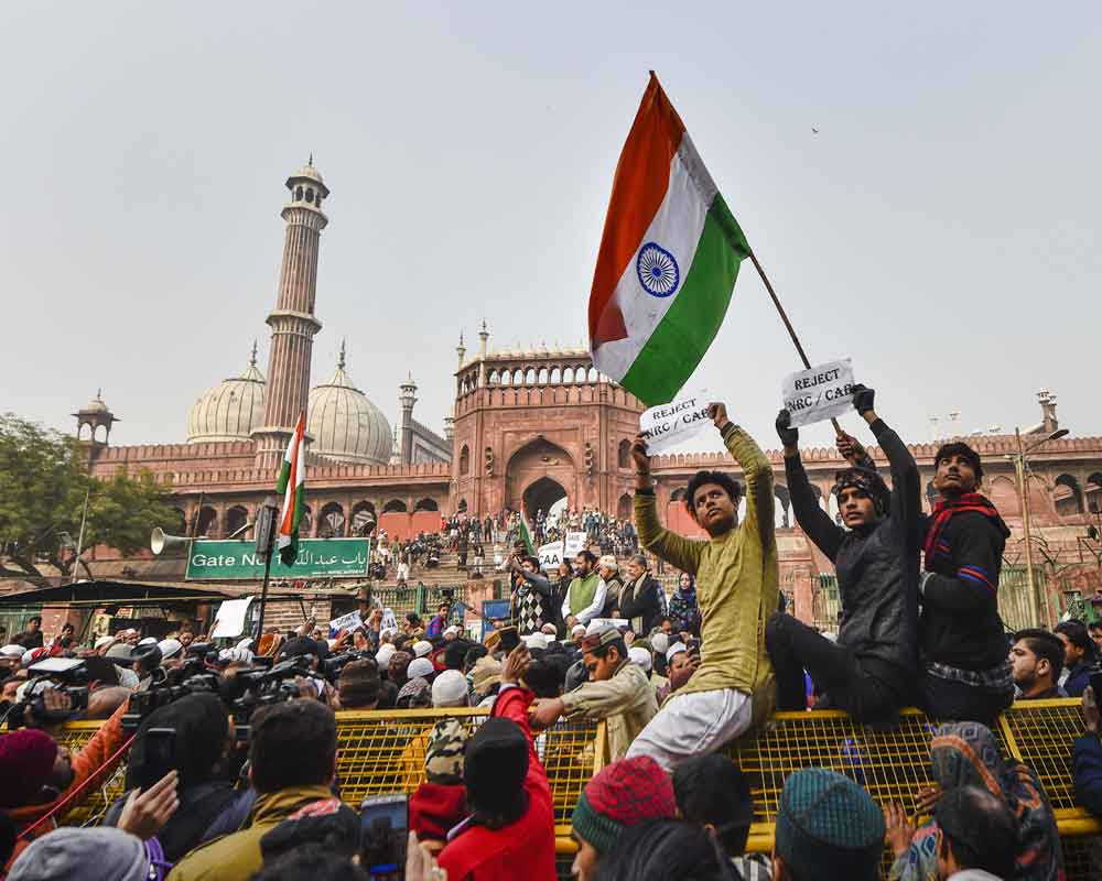 A protestor holds the national flag during a protest against Citizenship (Amendment) Act, after Friday prayers, at Jama Masjid in New Delhi - PTI