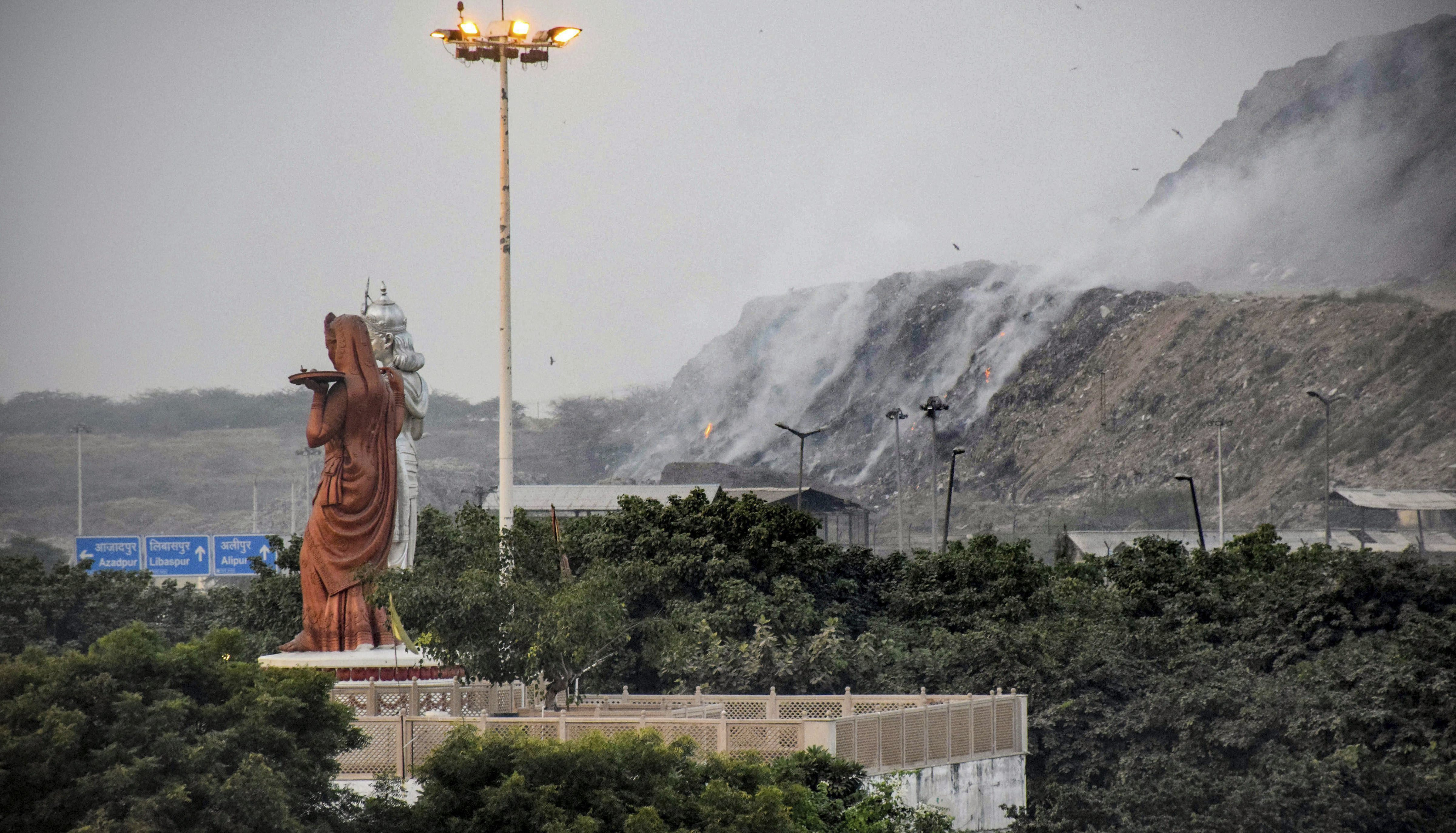 Smoke rises after a fire broke out at Bhalswa landfill site in New Delhi - PTI