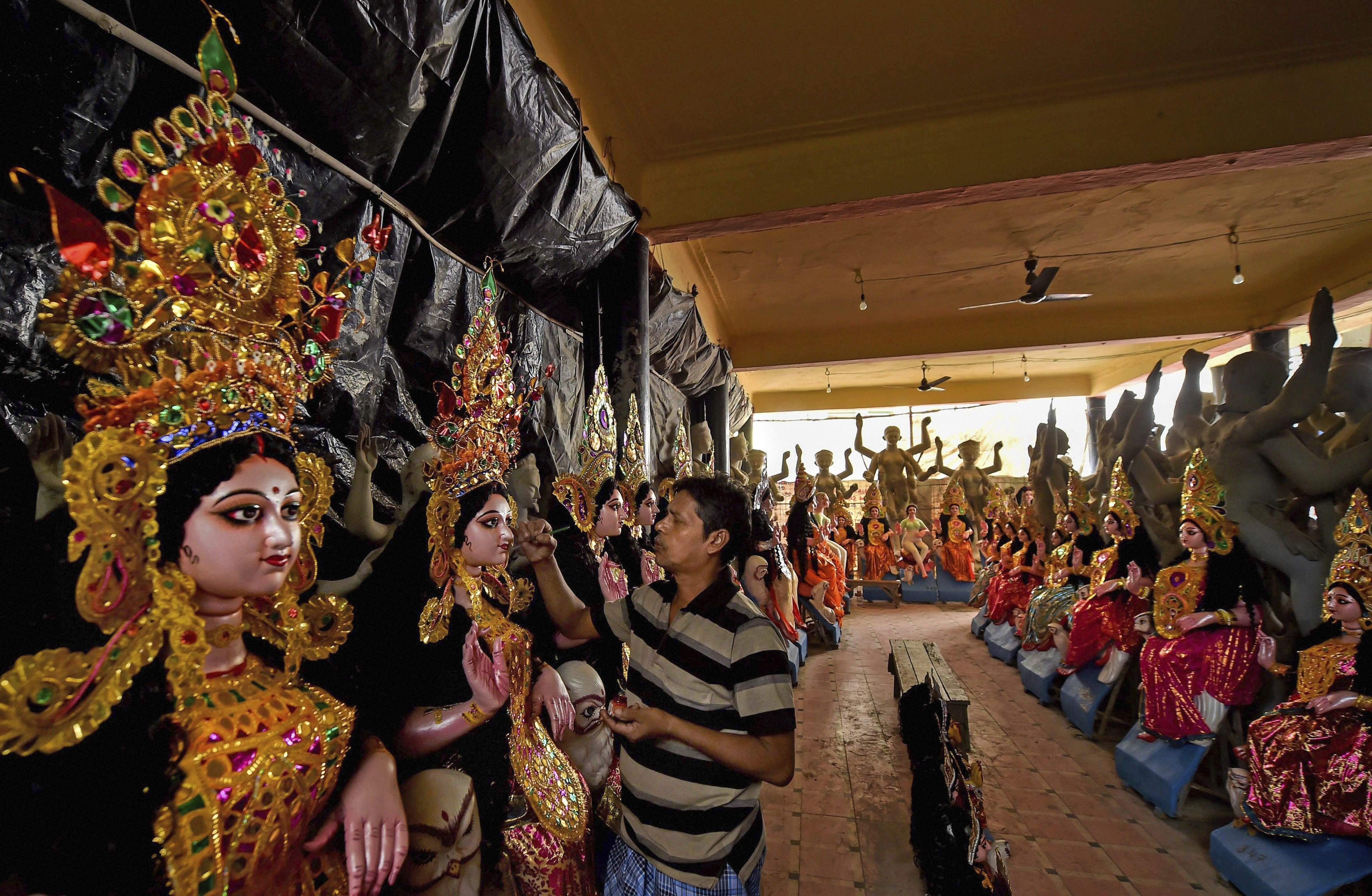 An artisan gives final touch to an idol of Goddess Lakshmi placed for sale ahead of Lakshmi puja, in Kolkata - AP