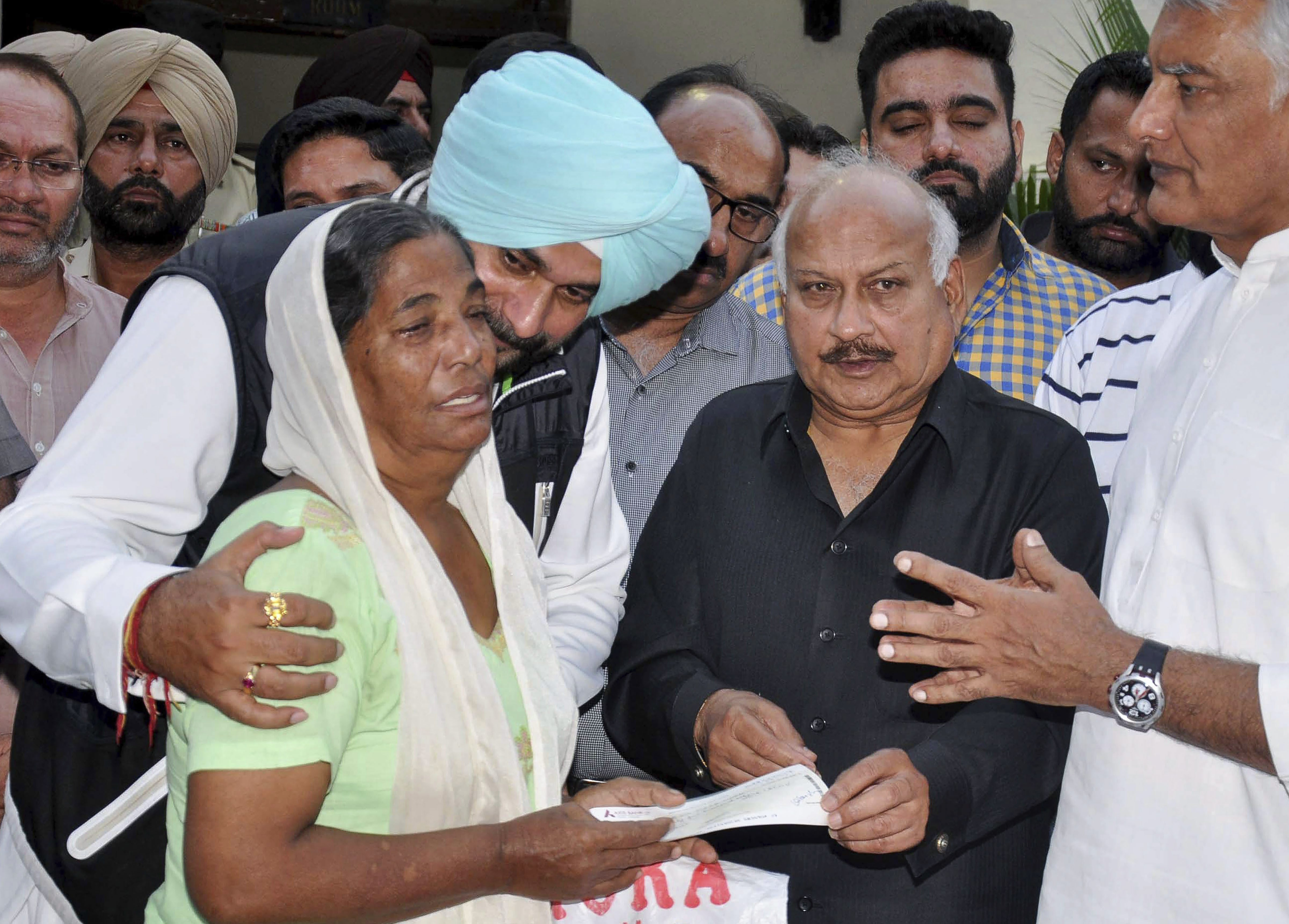 Punjab Cabinet ministers Navjot Singh Sidhu and Brahm Mohindra along with Punjab Pradesh Congress Committee (PPCC) President Sunil Jakhar gives away compensation cheques to the victims of Joda Phatak mishap, in Amritsar - PTI